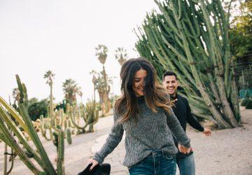 glückliches Paar, das zwischen Kakteen läuft