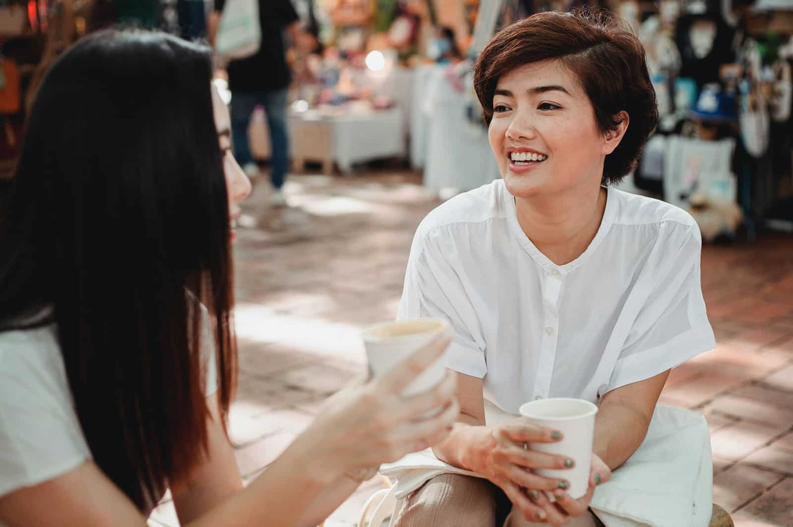 Zwei Frauen unterhalten sich im Straßencafé und trinken Kaffee