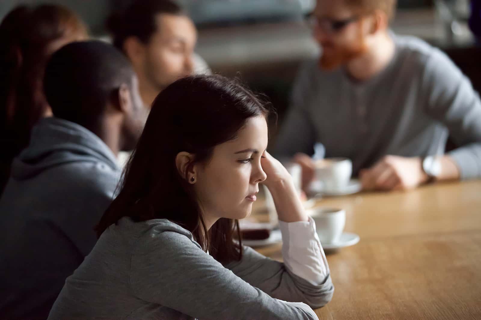 ein Mädchen, das alleine sitzt und Freunde ignoriert im Cafe sitzen