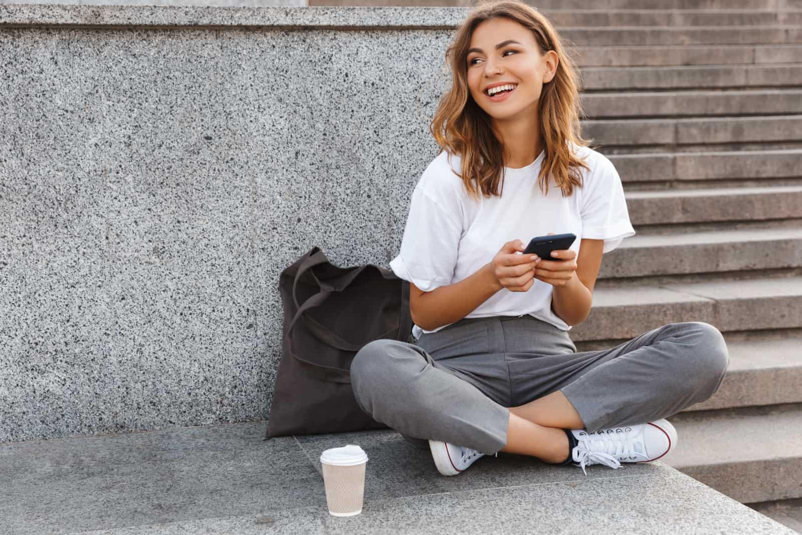 ein Mädchen sitzt auf dem Boden und einen Schlüssel auf ihrem Handy