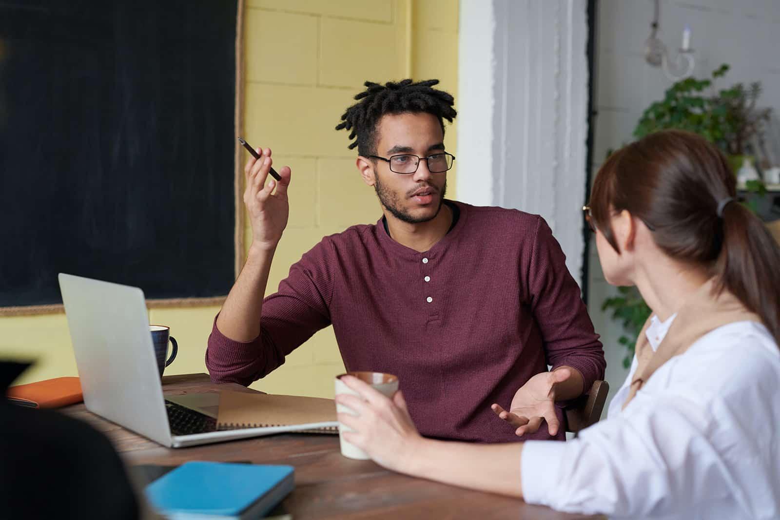 Ein Mann hält einen Stift und spricht mit einer Kollegin, während er zusammenarbeitet