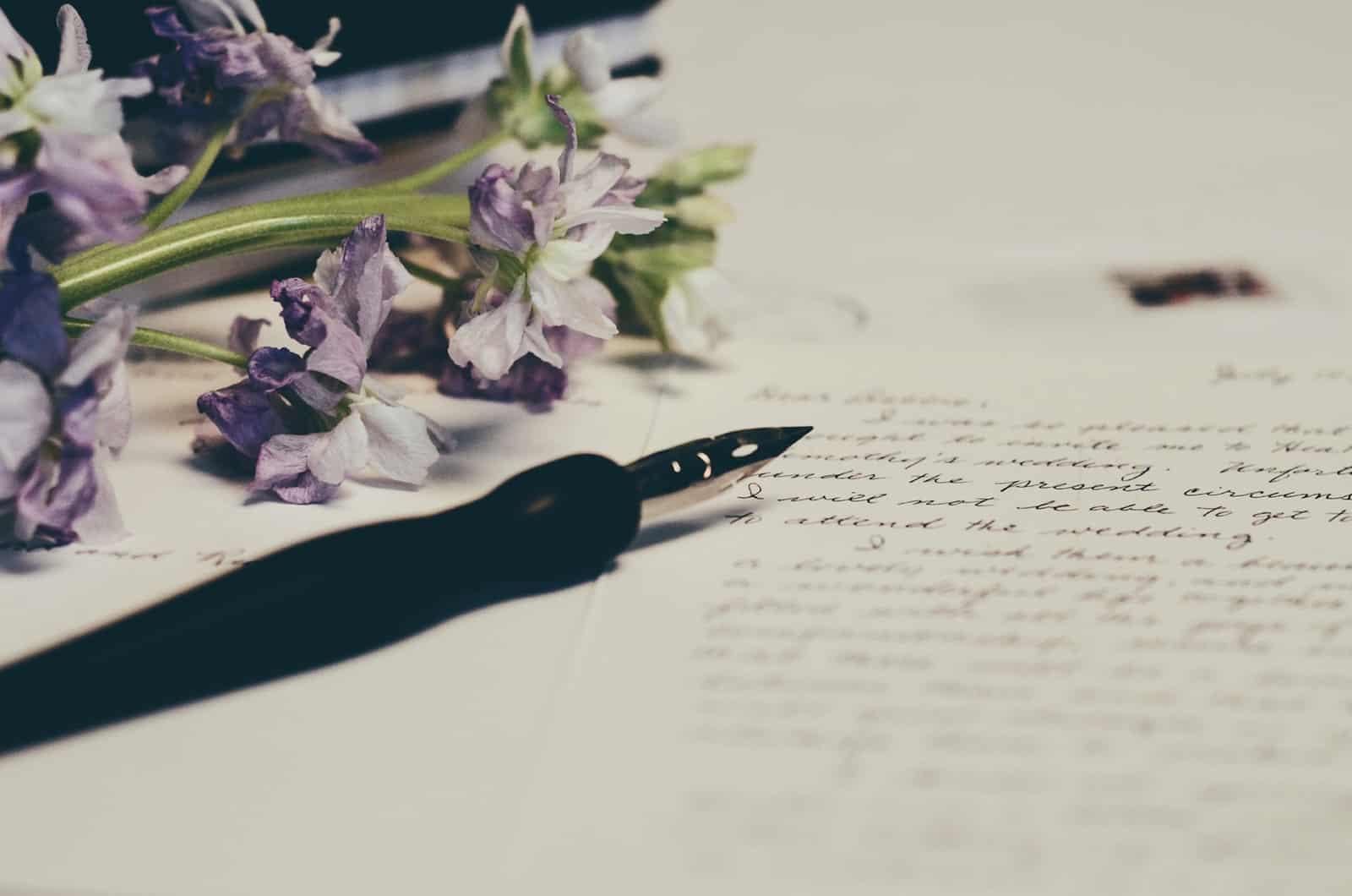 ein Stift und ein Liebesbrief mit lila Blumen daneben