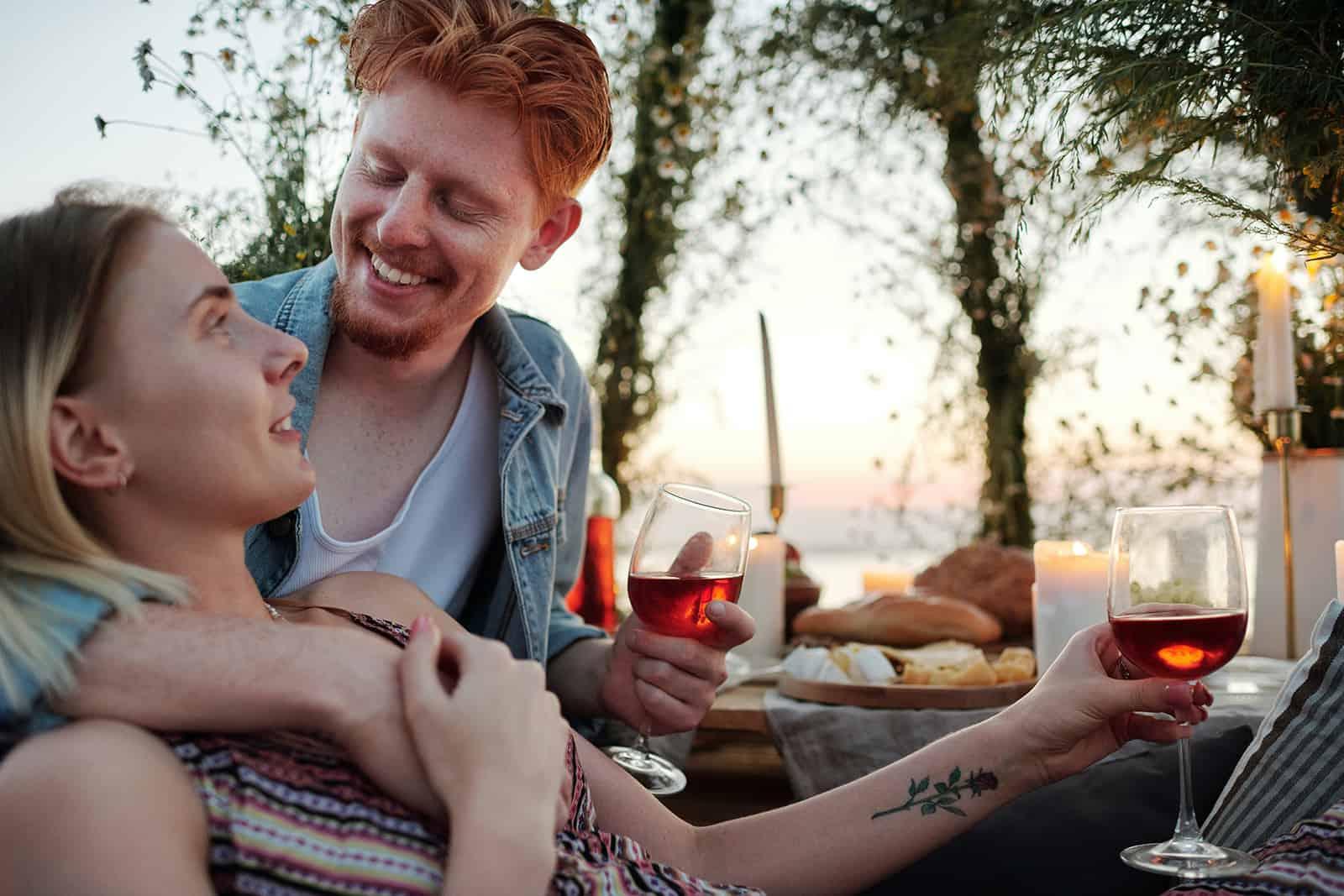 ein glückliches Paar, das während des romantischen Abendessens Wein trinkt