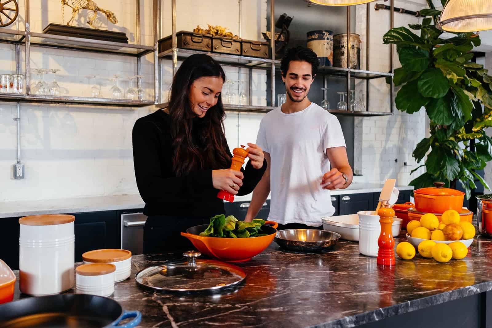 ein glückliches Paar, das in der Küche steht, während es eine Mahlzeit zubereitet