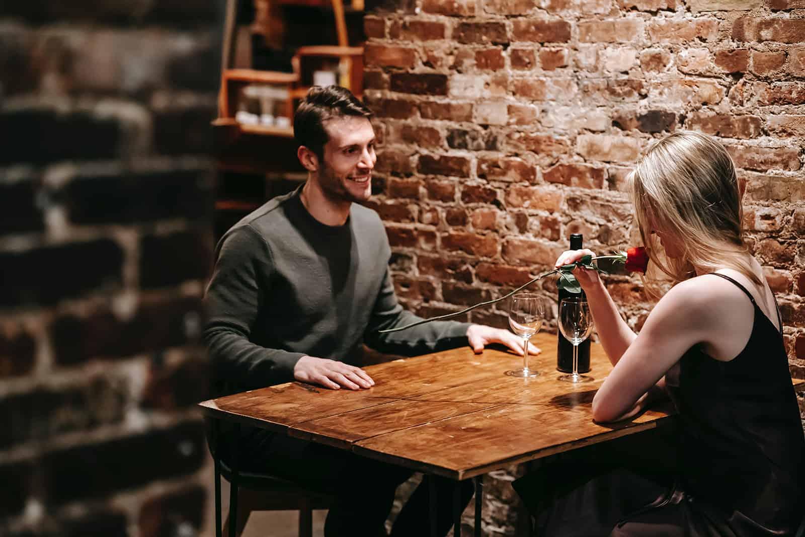 Ein lächelnder Mann, der elegante Frau betrachtet, die mit ihm im Restaurant sitzt und Rose riecht