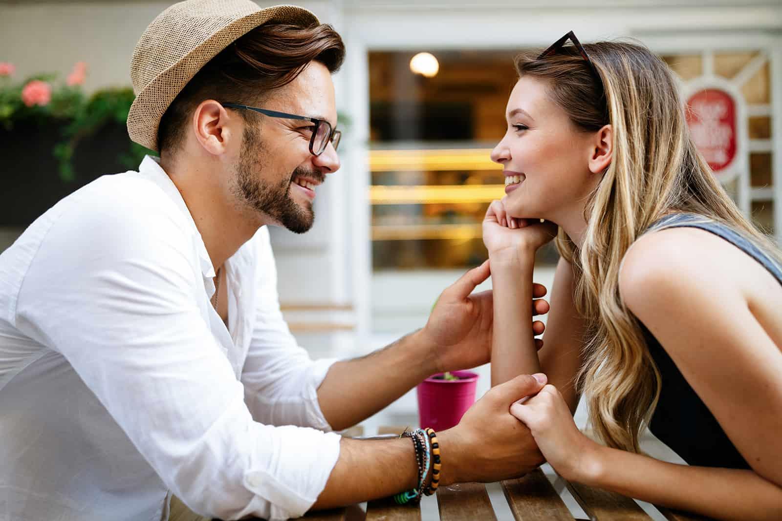 ein lächelndes Paar, das im Café Hände hält und sich ansieht
