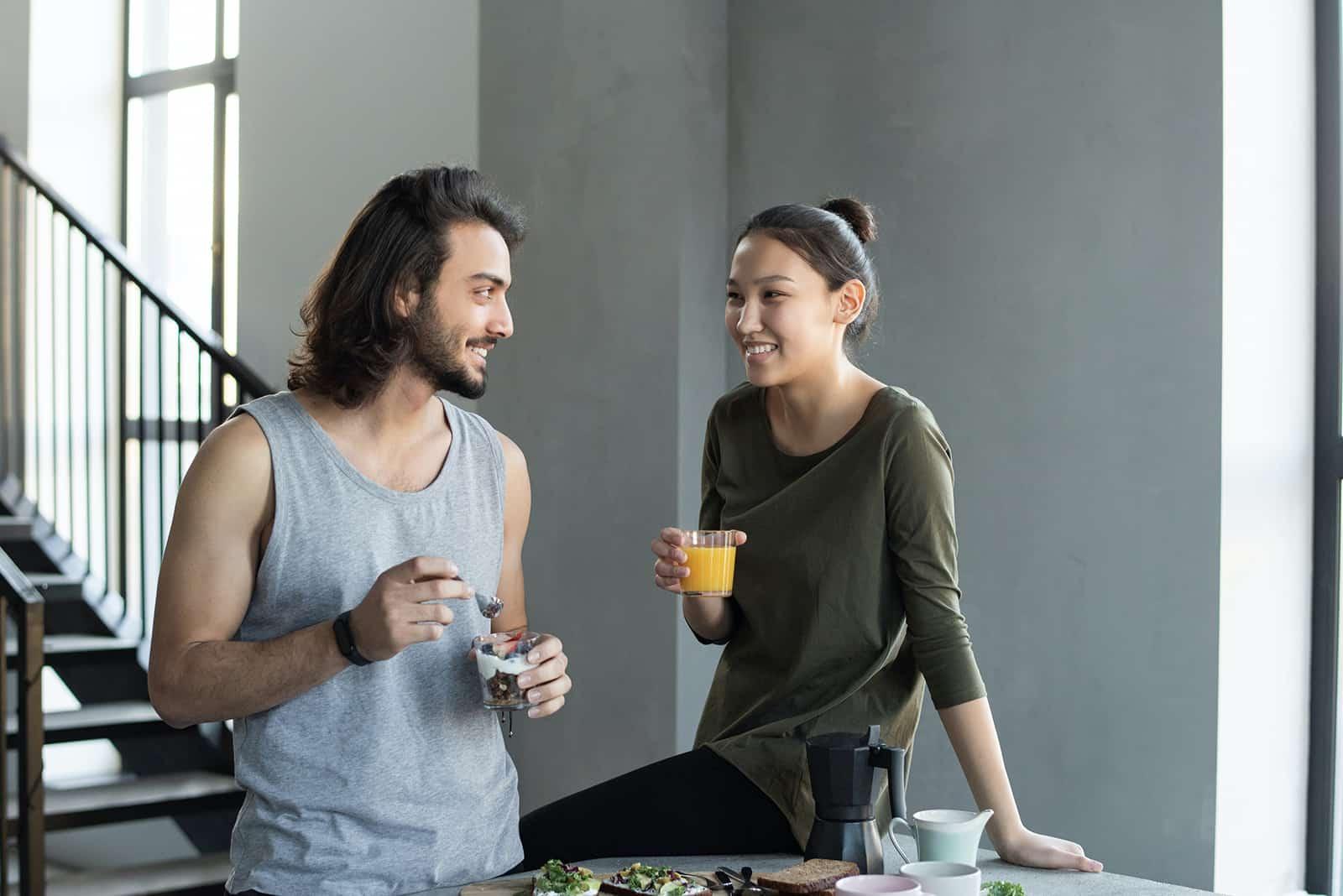 ein lächelndes Paar, das zusammen zu Hause frühstückt