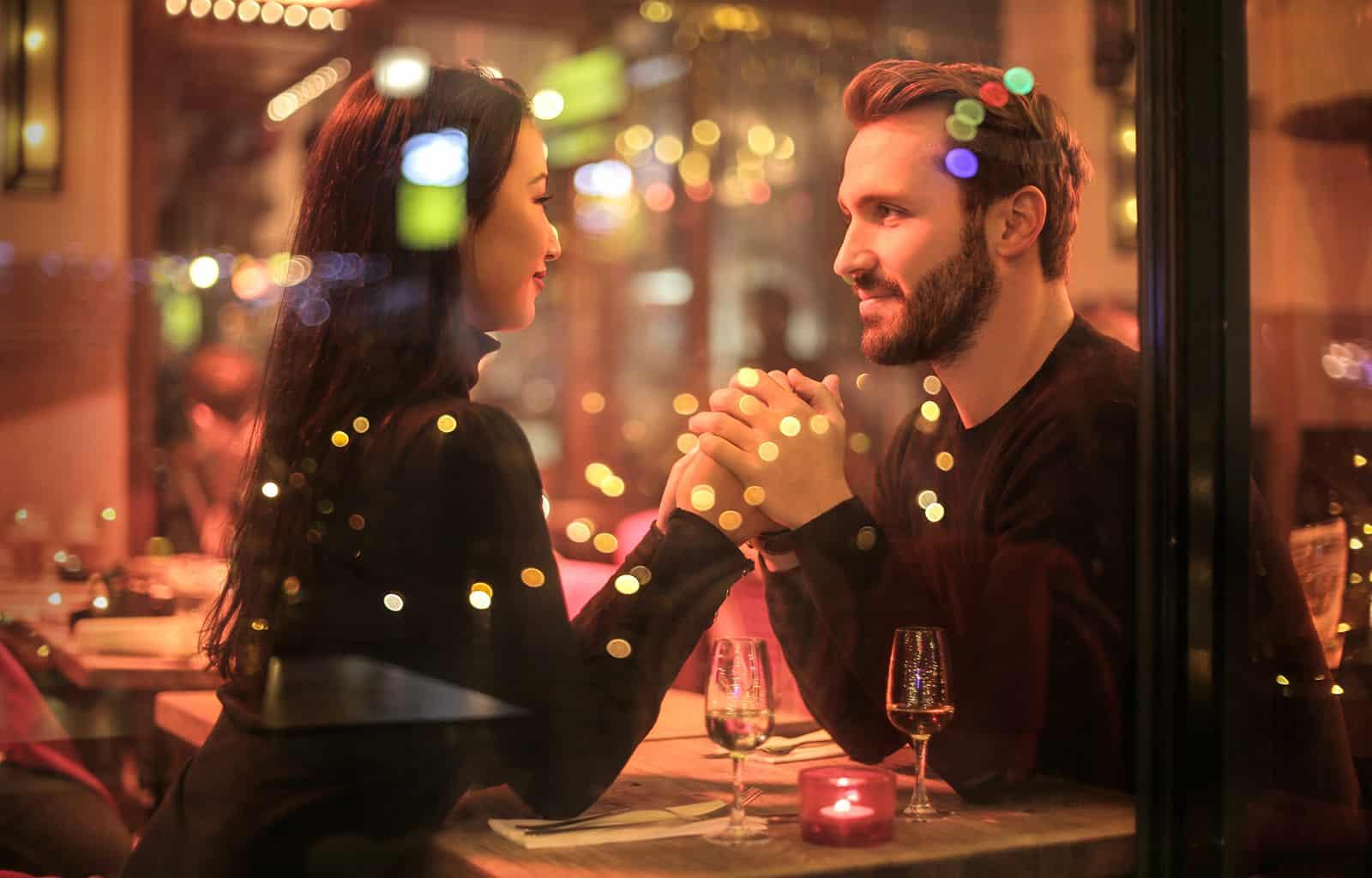 ein liebevolles Paar Händchen haltend in einem romantischen Restaurant