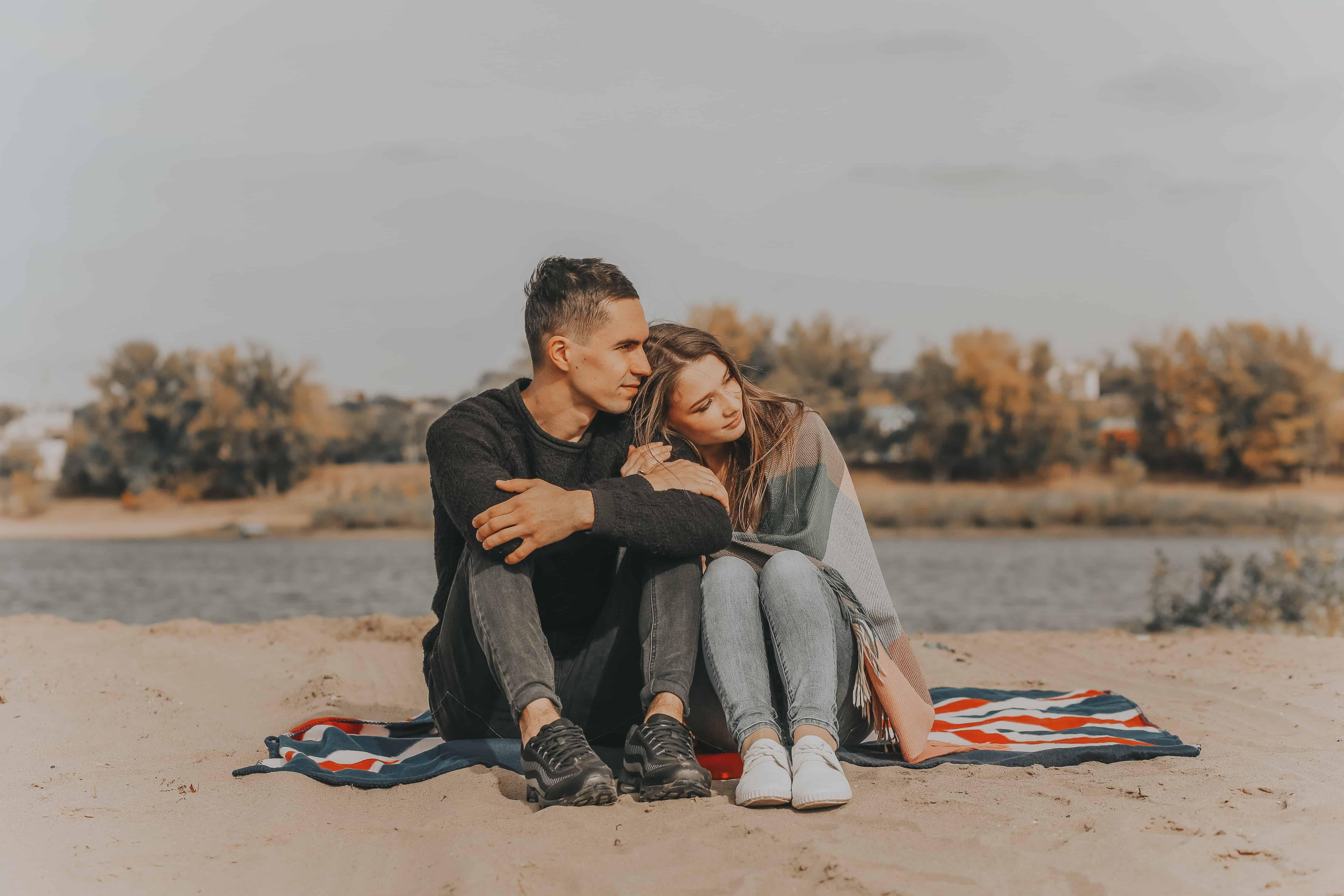 ein liebendes Paar sitzt auf der Decke am Strand