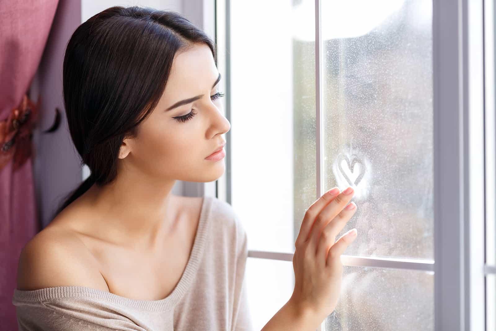 ein nachdenkliches Mädchen, das auf der Fensterbank sitzt und ein Herz auf Glas malt