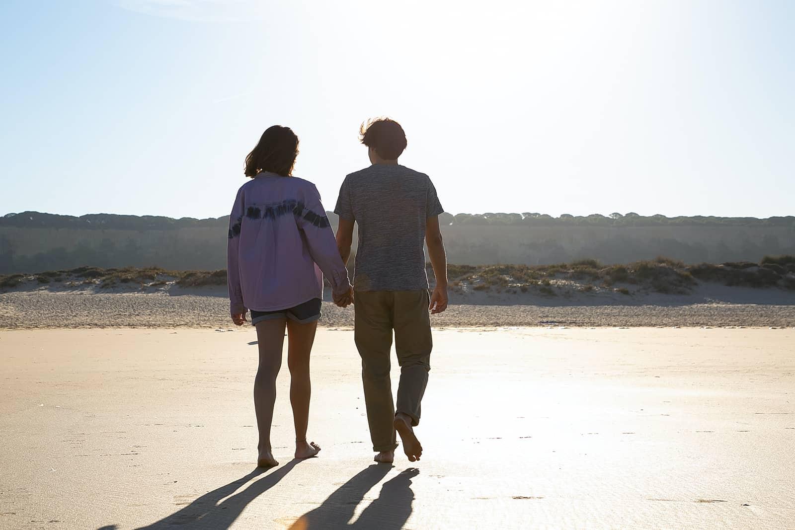 Ein Paar geht am Strand spazieren und hält sich an den Händen