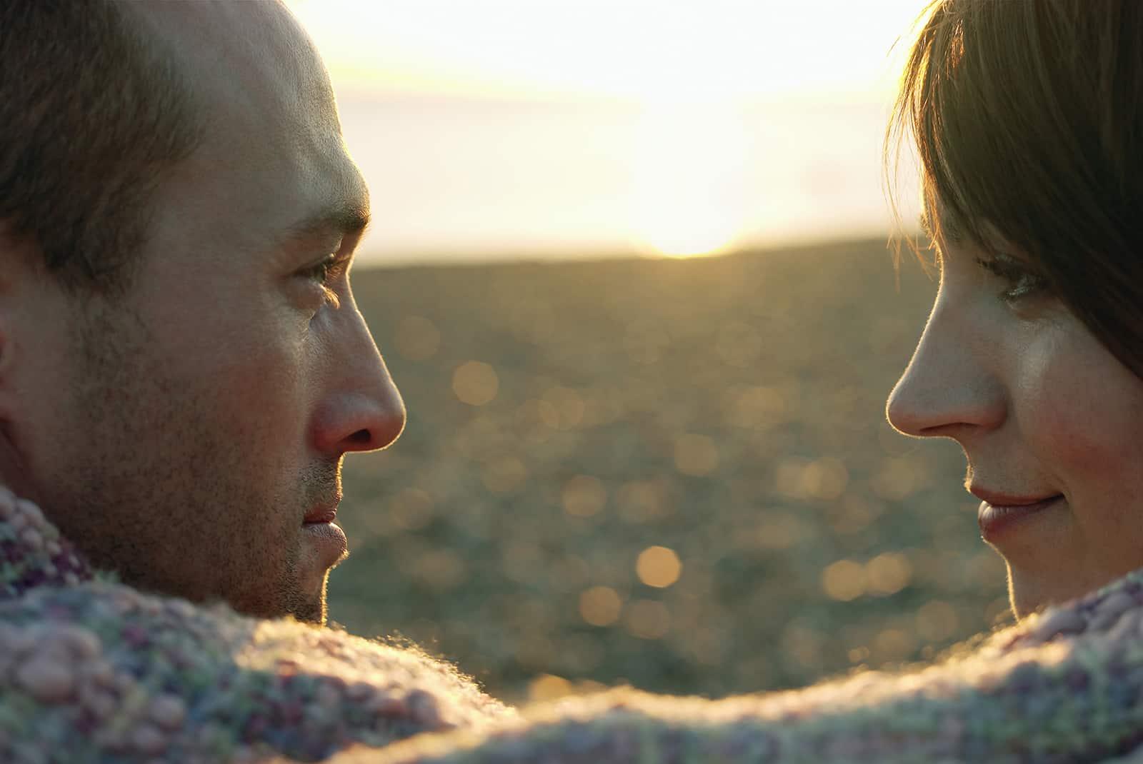 ein Paar, das sich in eine Decke am Strand gewickelt ansieht