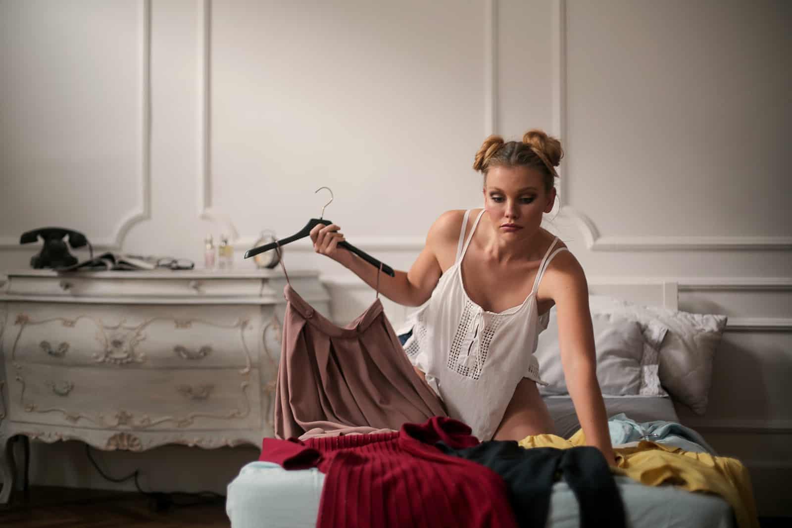 eine Frau, die ein Outfit auswählt, während sie auf dem Bett sitzt
