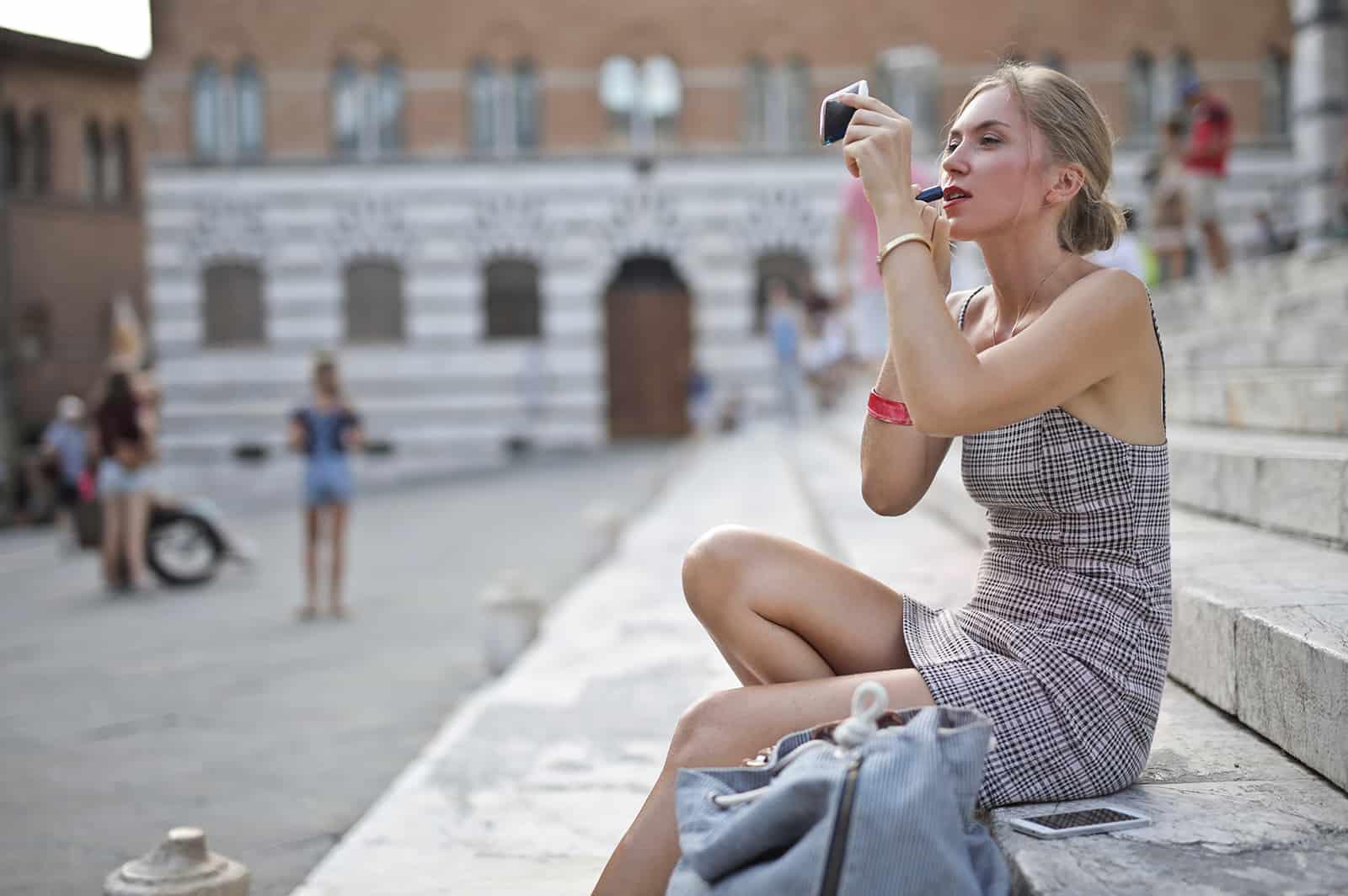 eine Frau, die einen Lippenstift aufträgt, während sie auf der Treppe in der Stadt sitzt