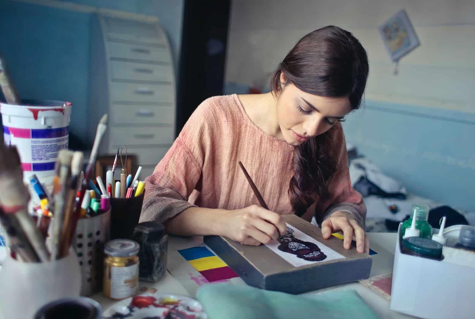 eine Frau, die mit einem Pinsel am Tisch malt