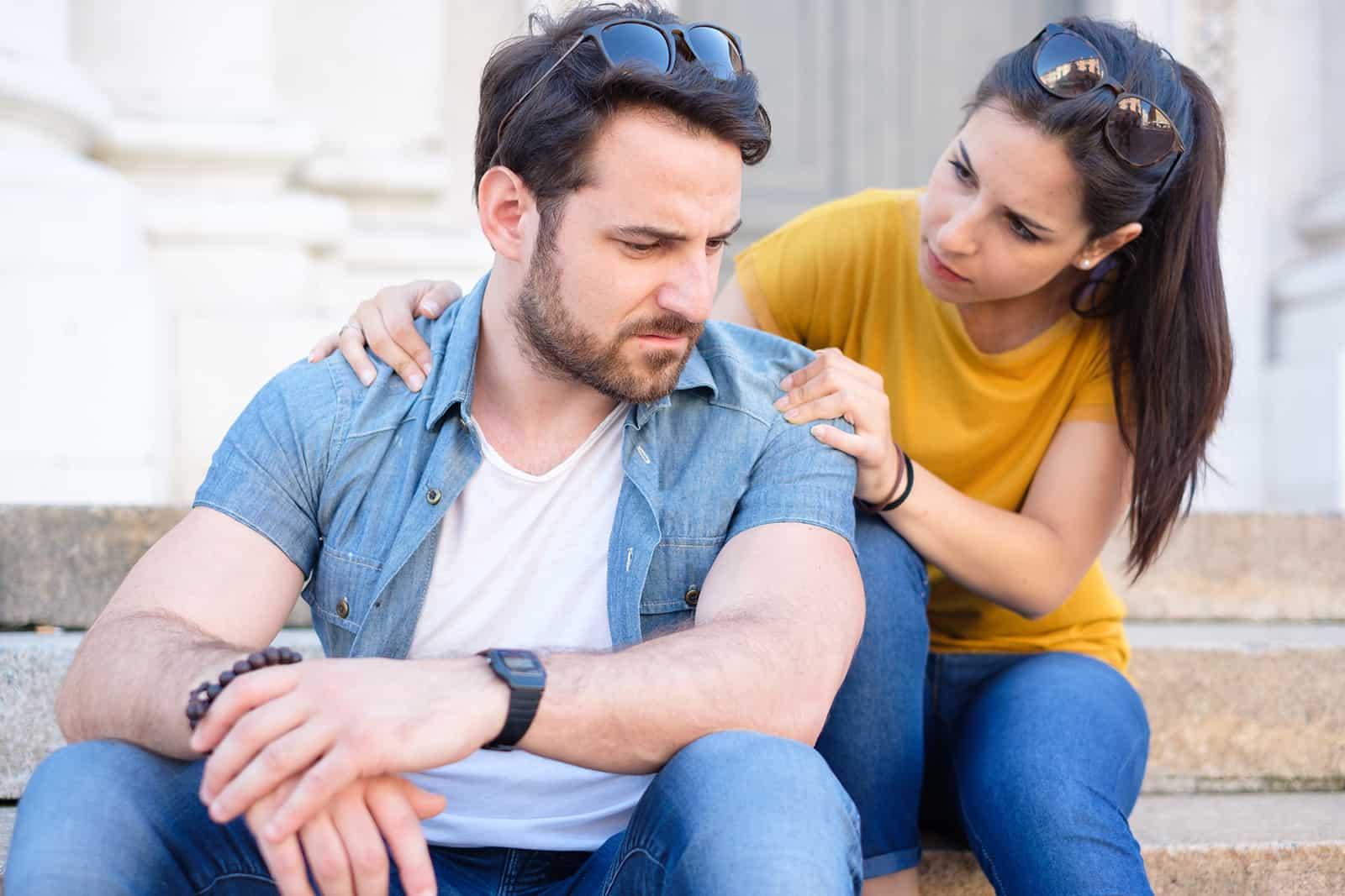 Eine Frau entschuldigt sich bei einem verärgerten Freund, der auf der Treppe sitzt