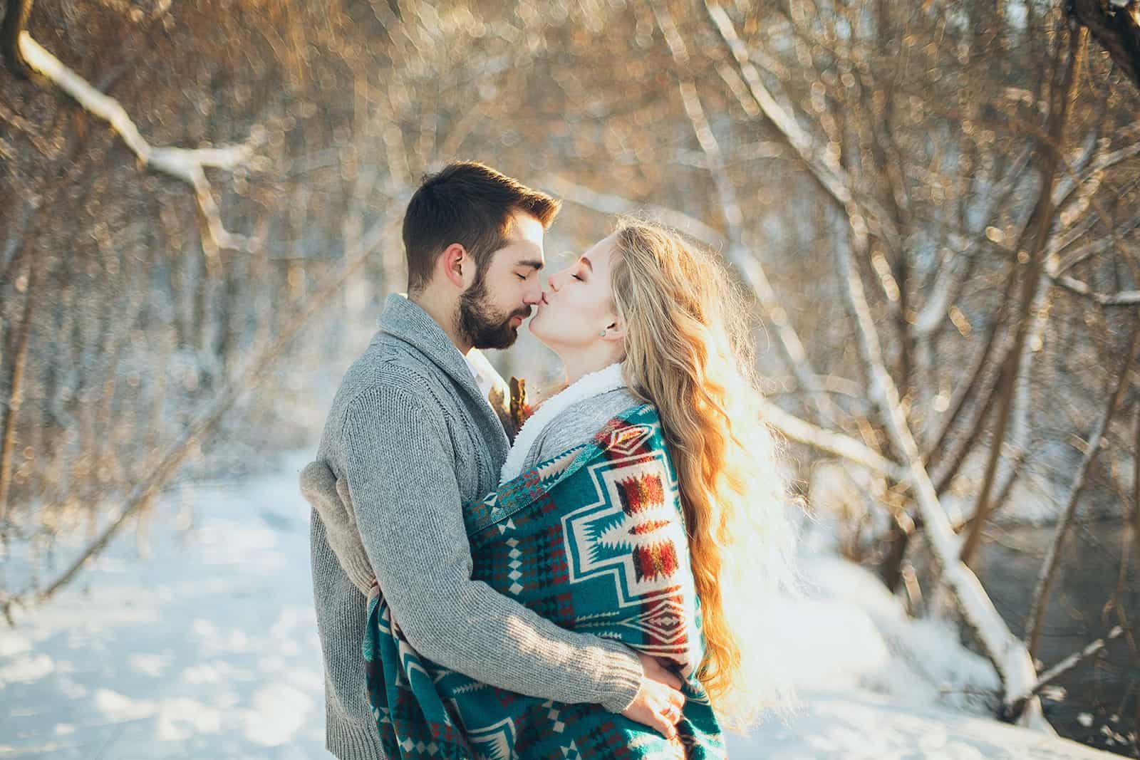 eine Frau küsst einen Mann in die Nase, während sie sich umarmt