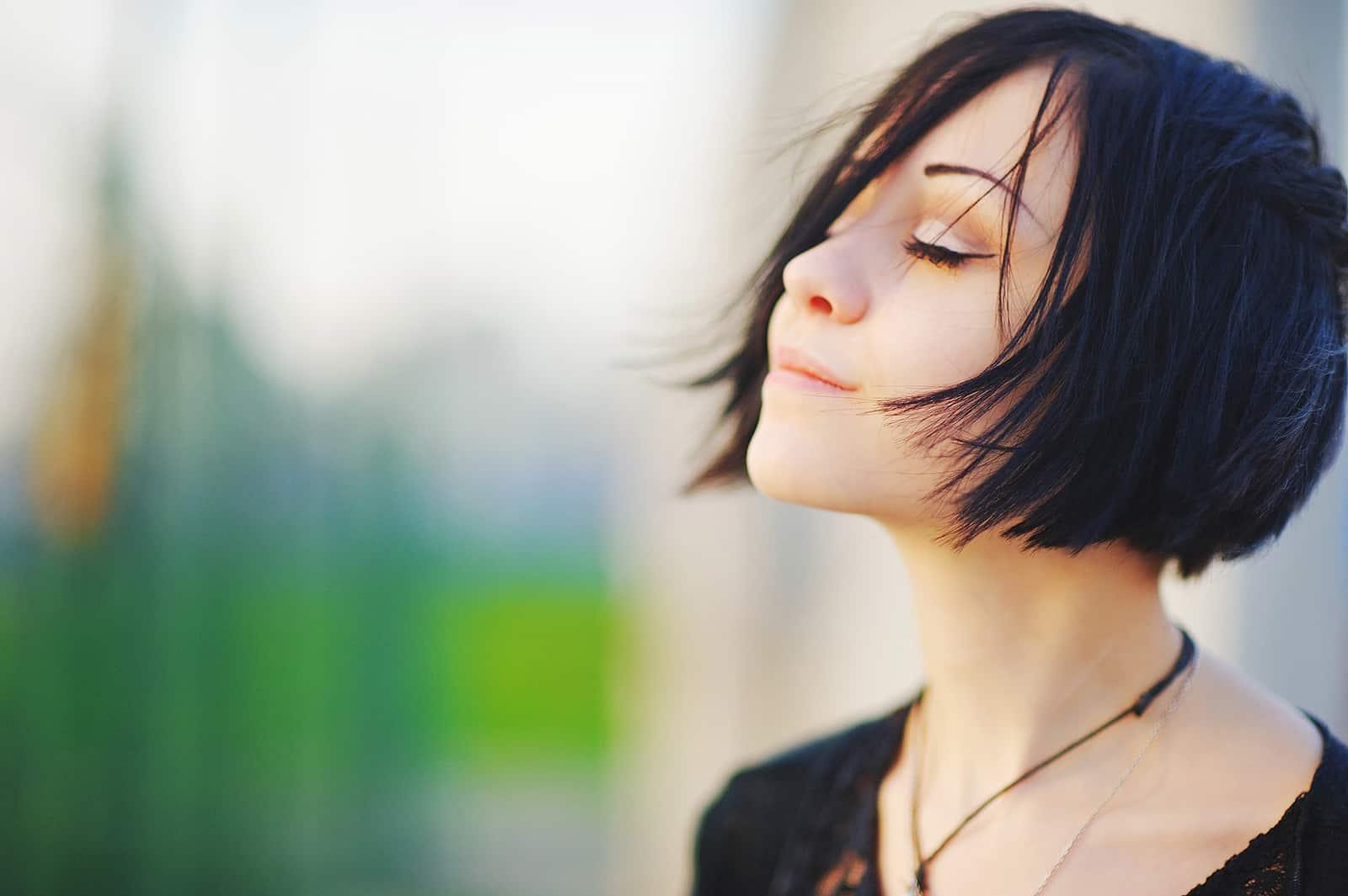 eine Frau mit geschlossenen Augen, die der Sonne zugewandt ist, während sie sich entspannt