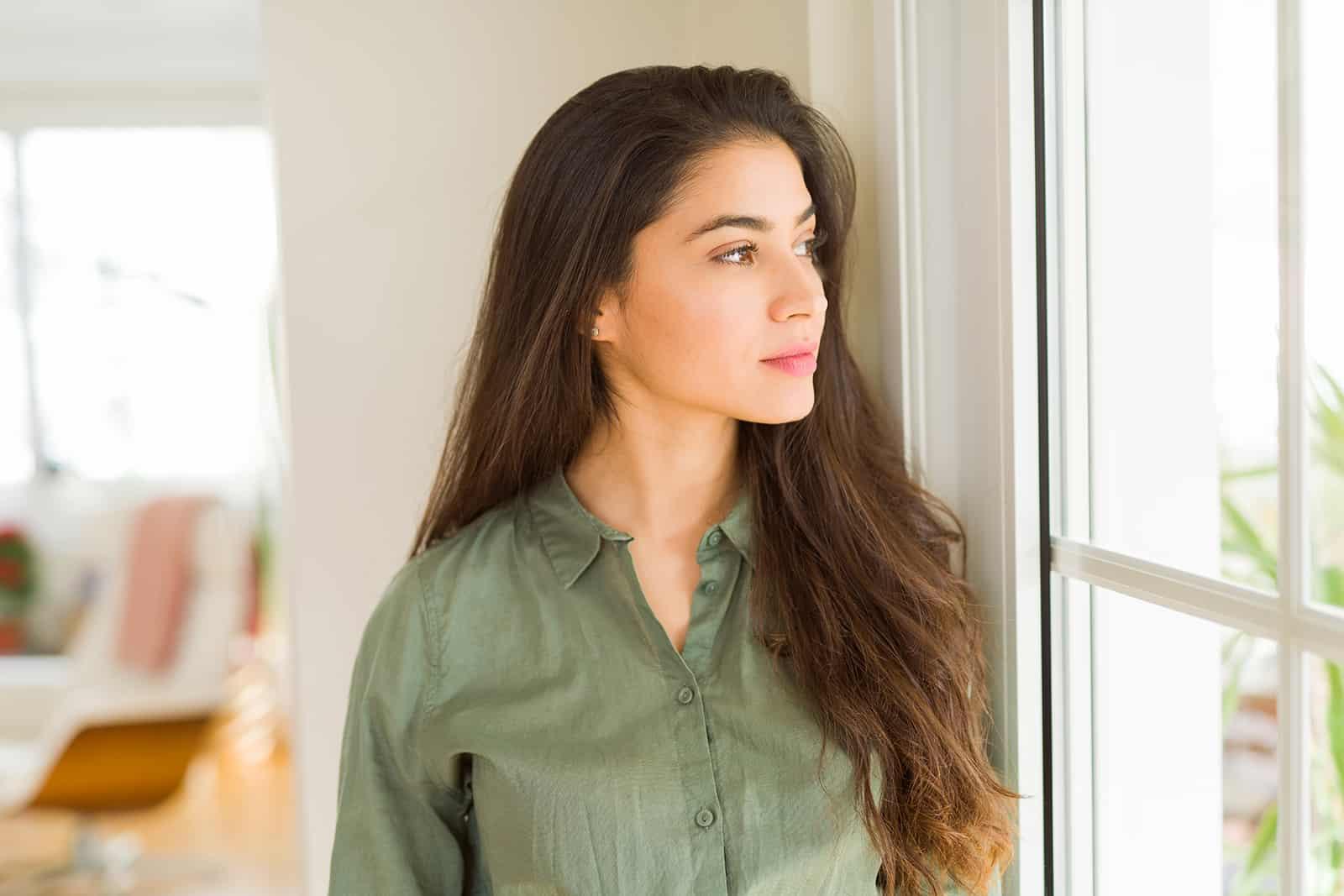 eine Frau mit langen Haaren, die nachdenklich aussieht und am Fenster steht
