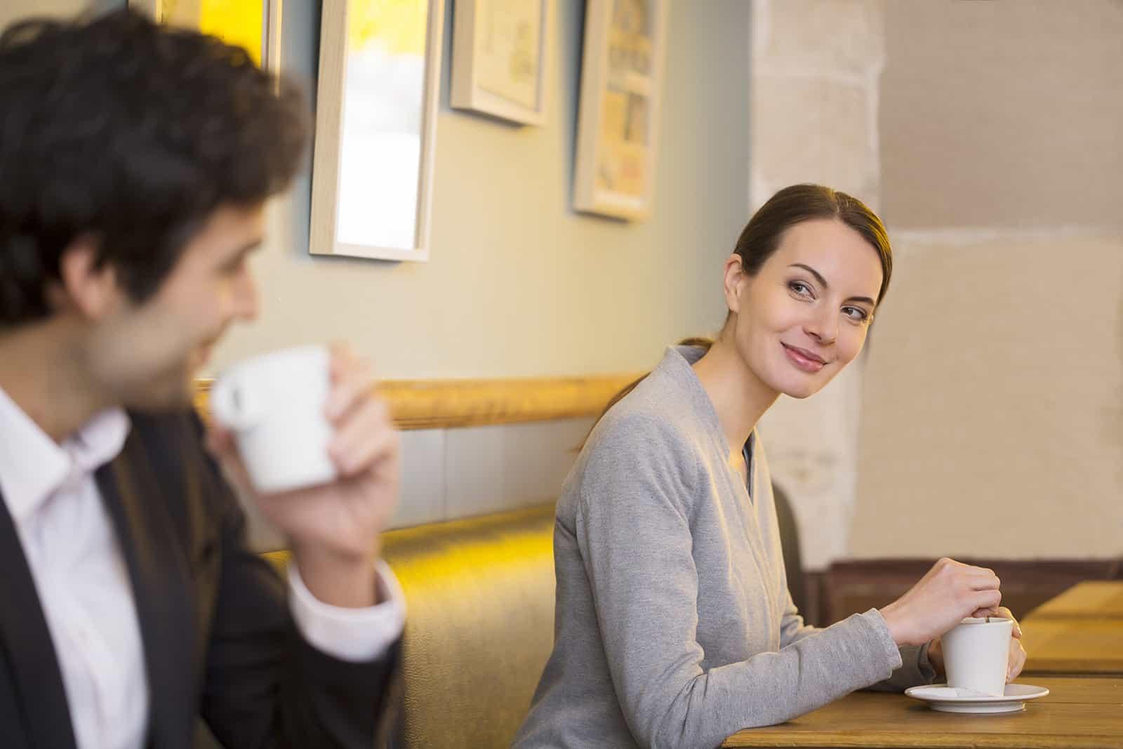 Eine Frau und ein Mann schauen sich in die Augen und flirten in einem Café