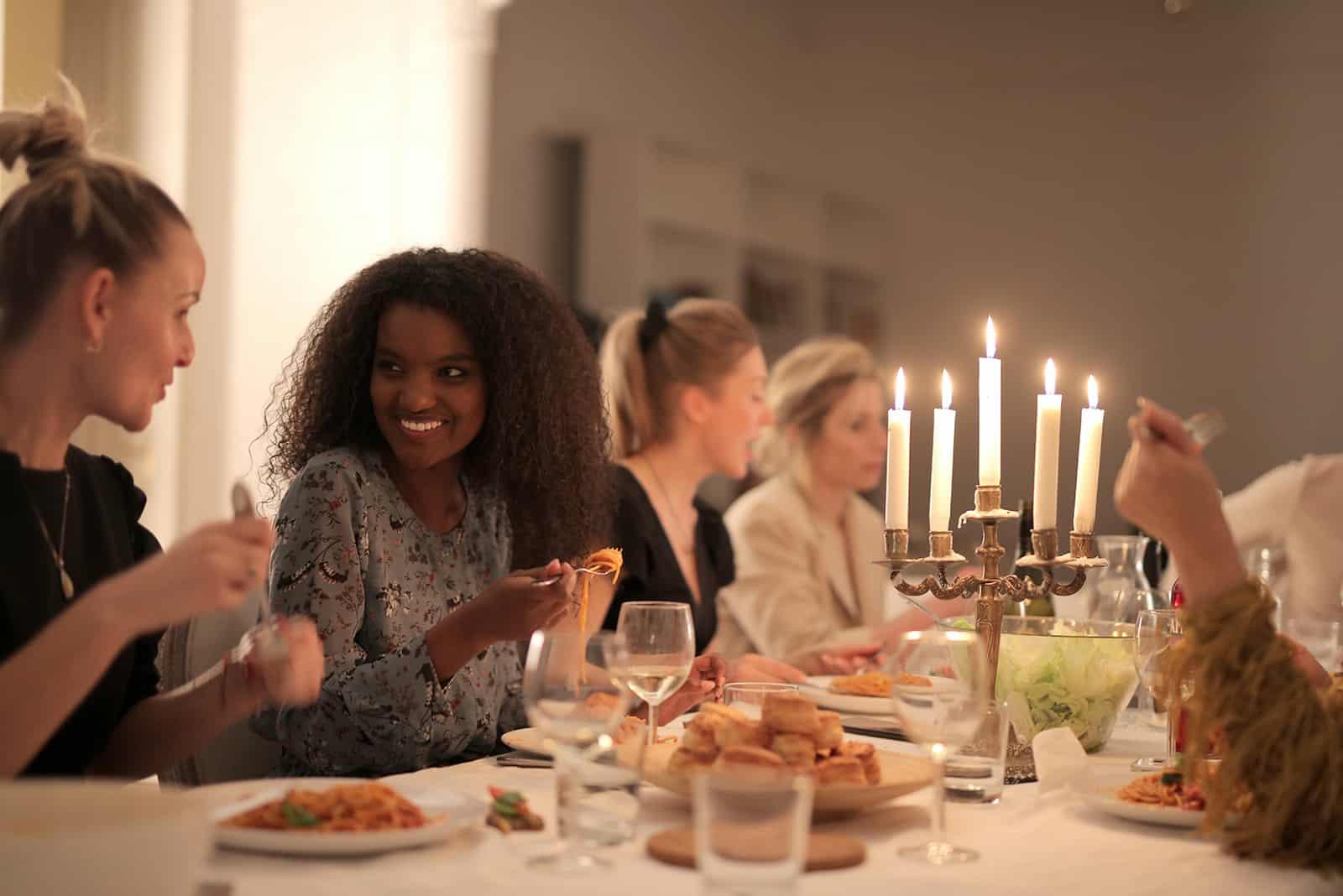 eine Gruppe von Frauen, die zu Abend essen, reden und lächeln