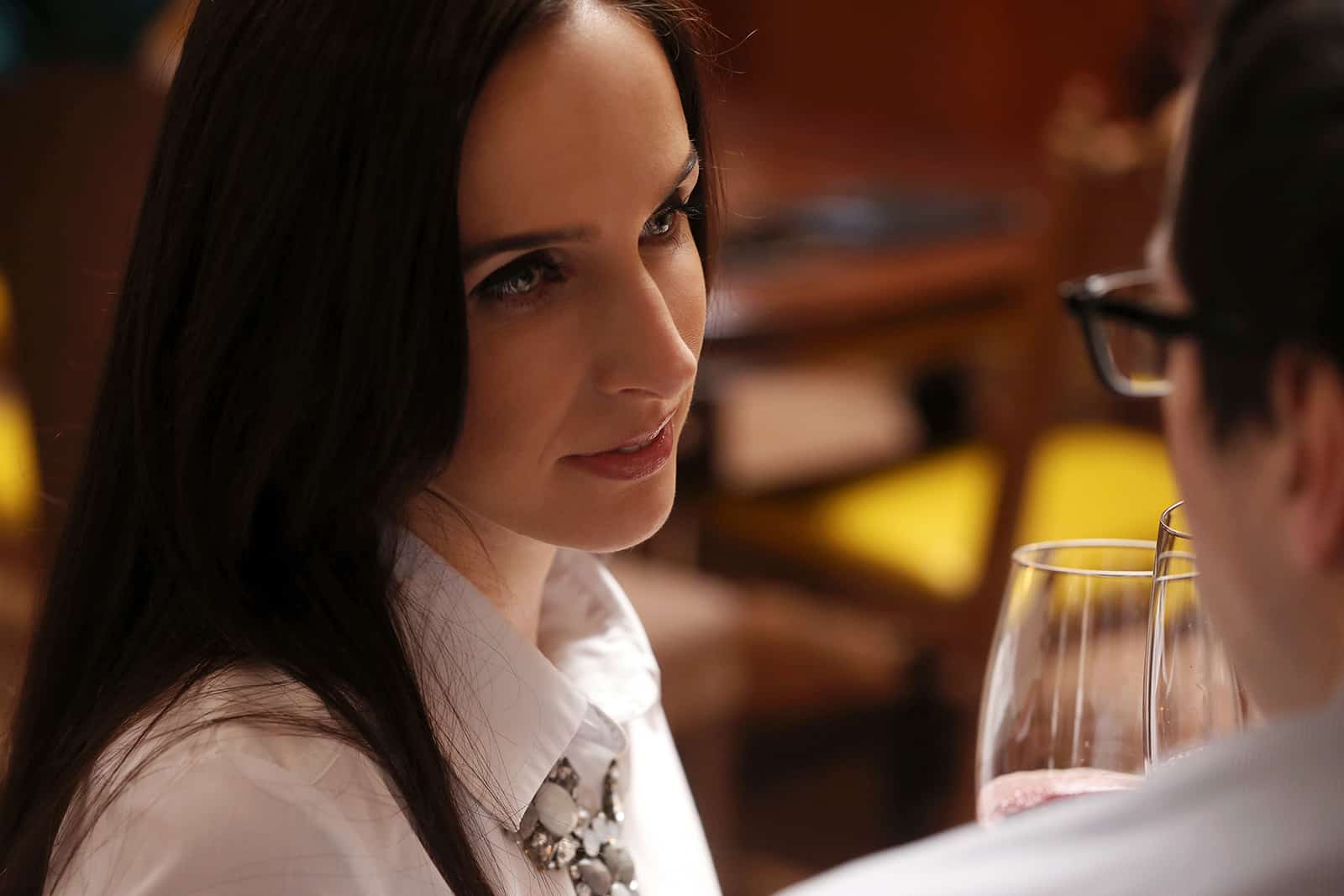 eine attraktive Frau, die Mann ansieht und mit Glas röstet