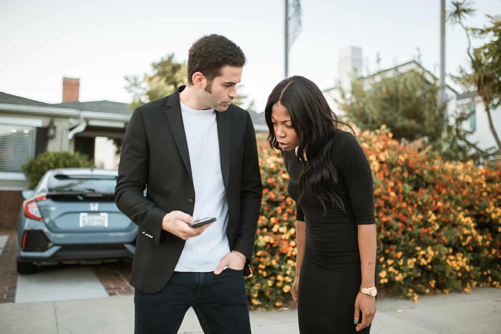 eine eifersüchtige Frau, die auf das Telefon ihres Freundes schaut, während sie zusammen auf der Straße steht