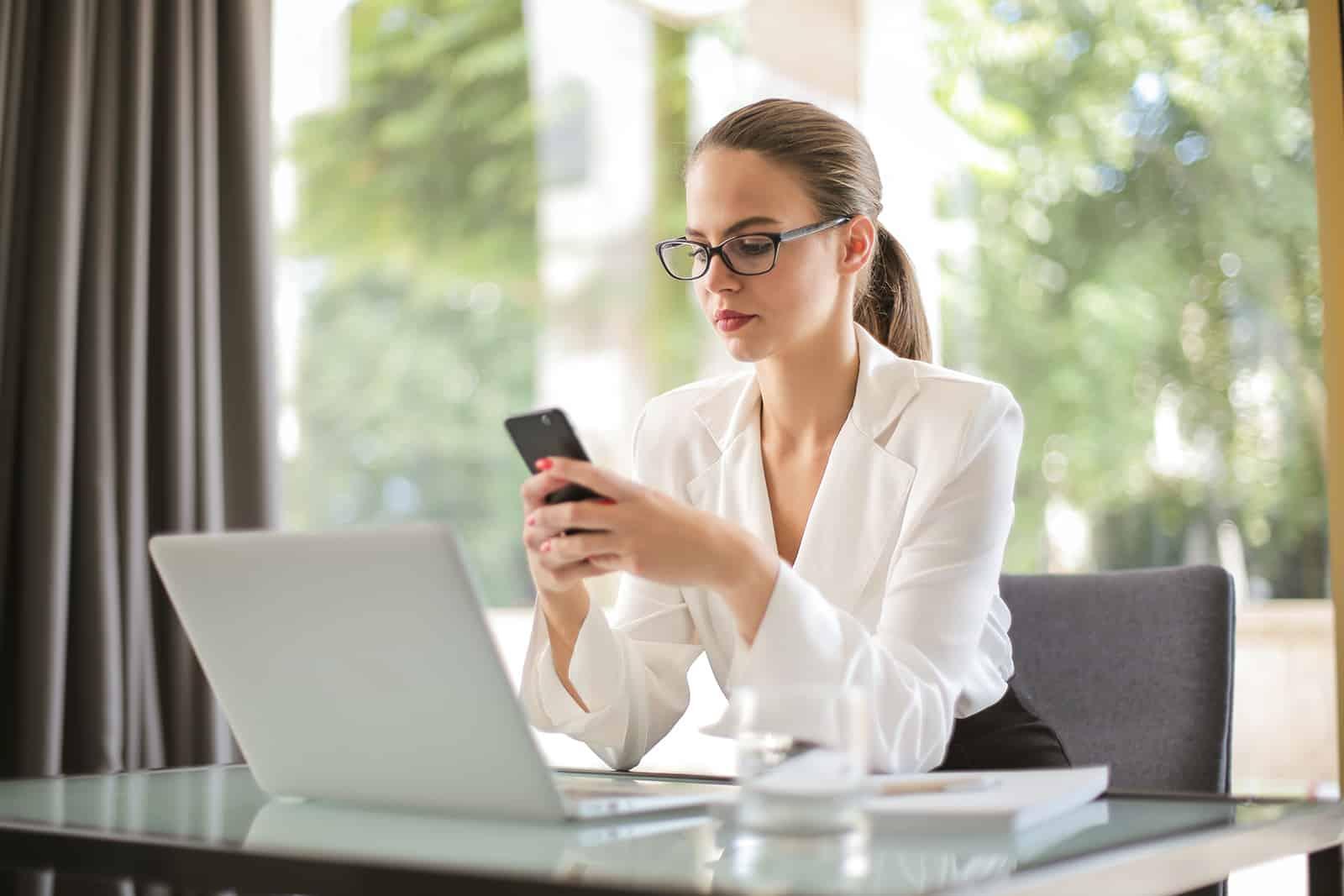 eine ernste Frau, die Smartphone betrachtet, das im Büro sitzt