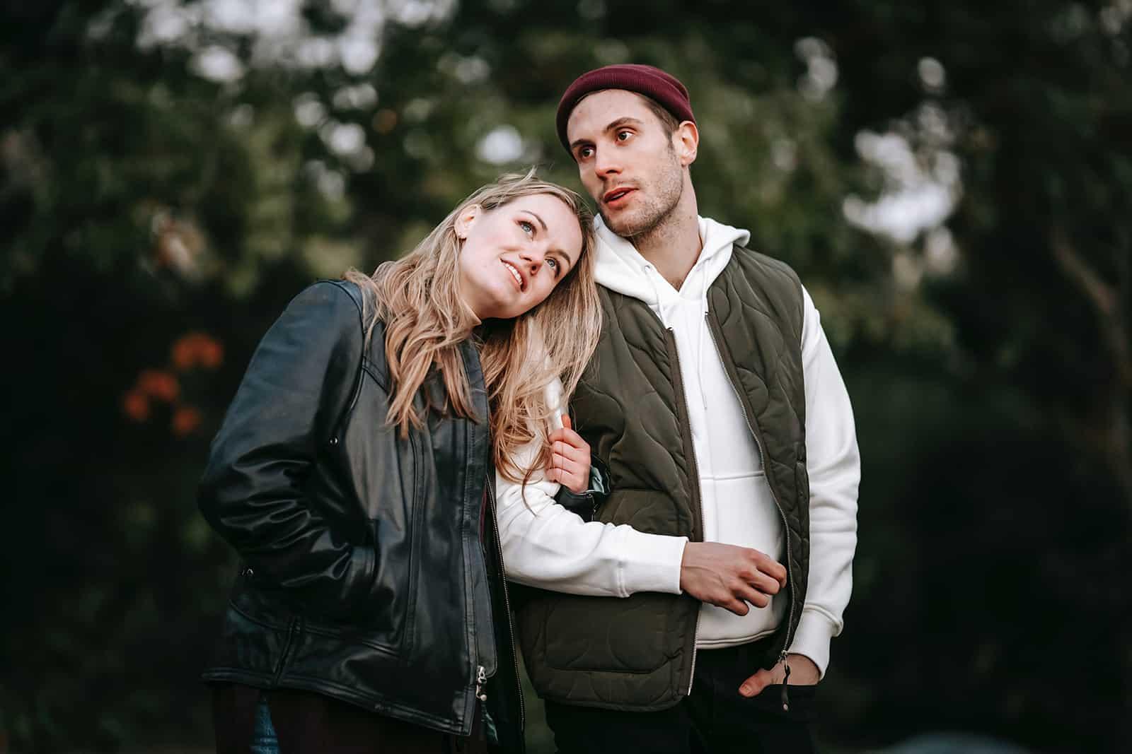 eine lächelnde Frau, die die Hand eines Mannes hält, während sie zusammen in einem Park gehen