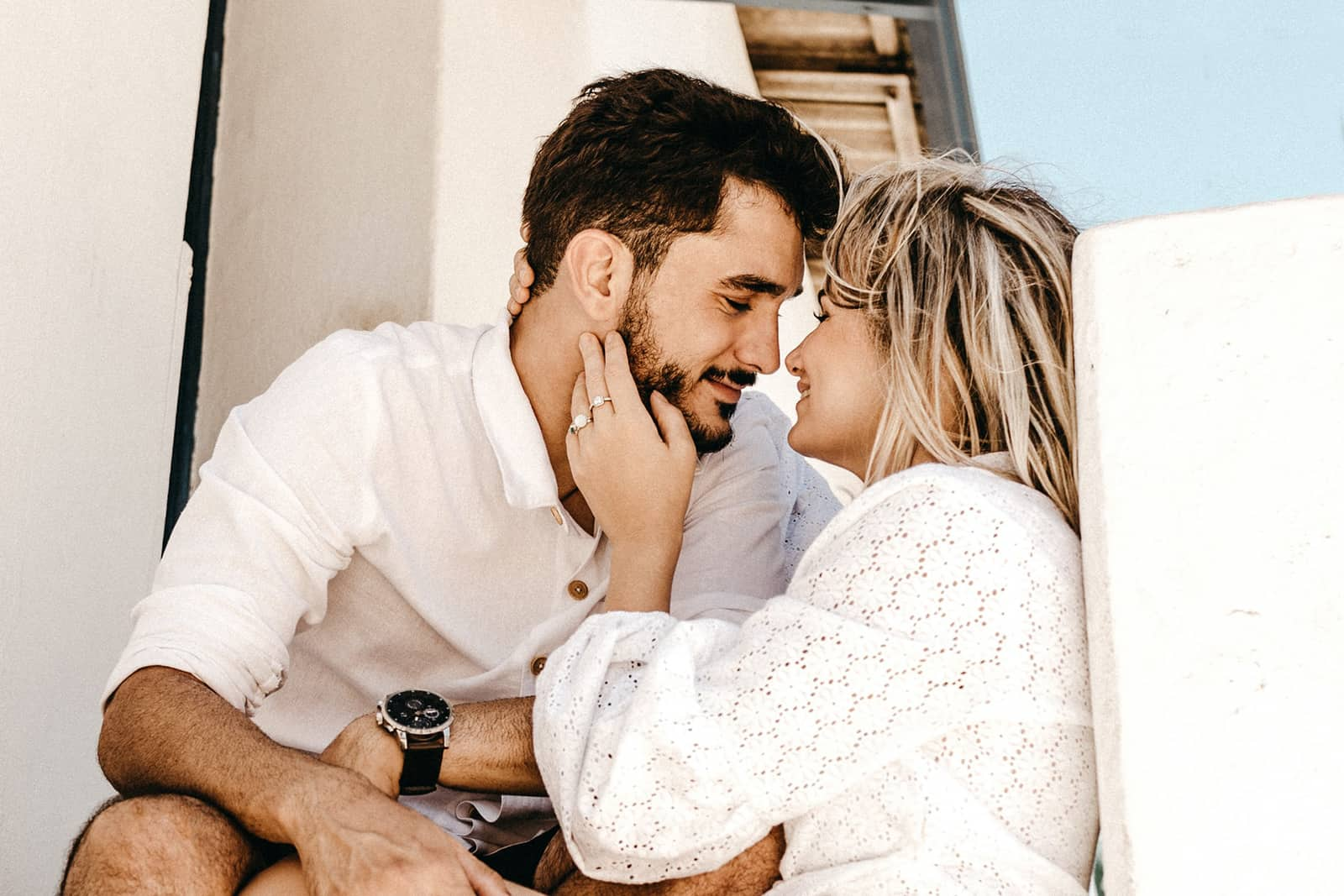 Eine lächelnde Frau, die das Gesicht ihres Mannes berührt, will sich küssen