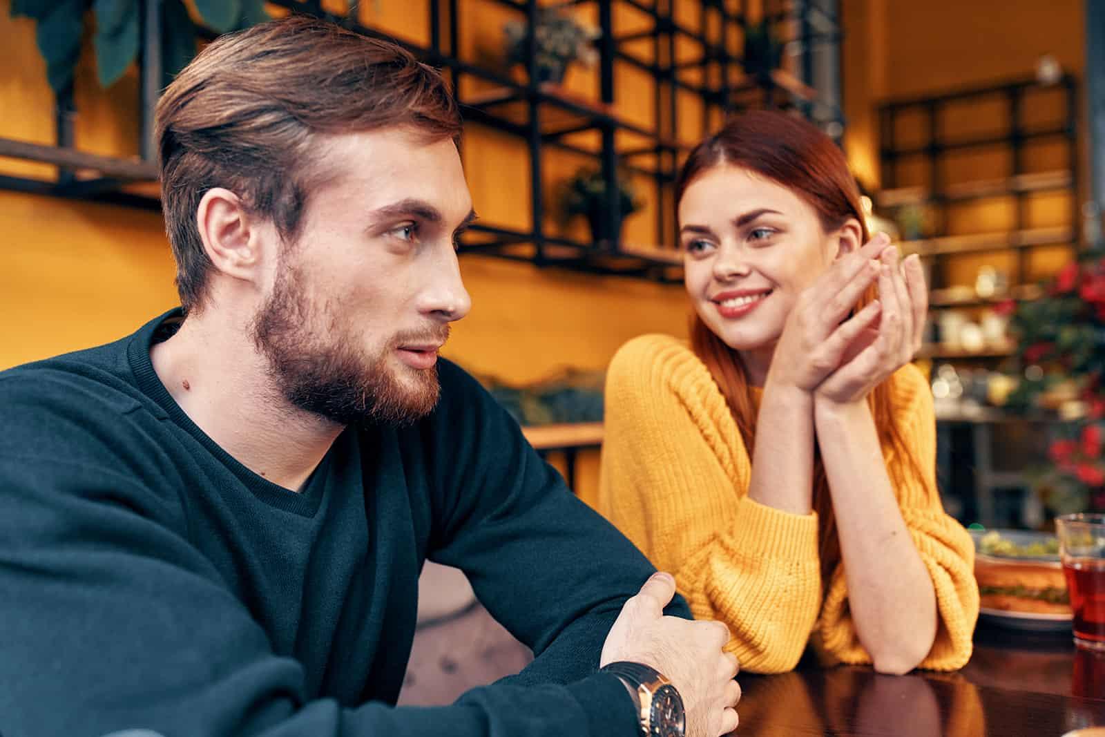 eine lächelnde Frau, die einen attraktiven Mann betrachtet, während sie zusammen im Café sitzen