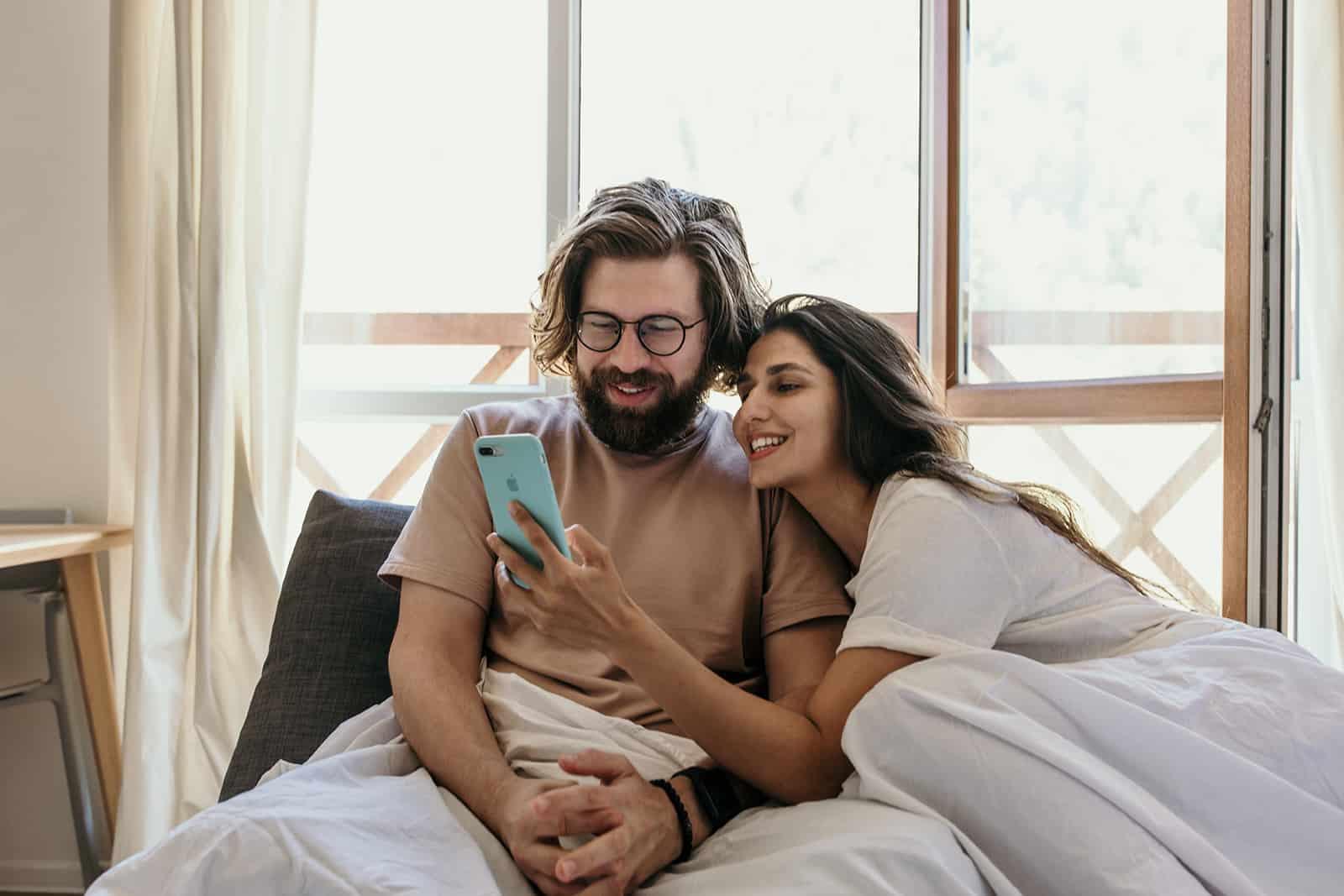 eine lächelnde Frau, die ihrem Freund ein Smartphone zeigt im Bett sitzen