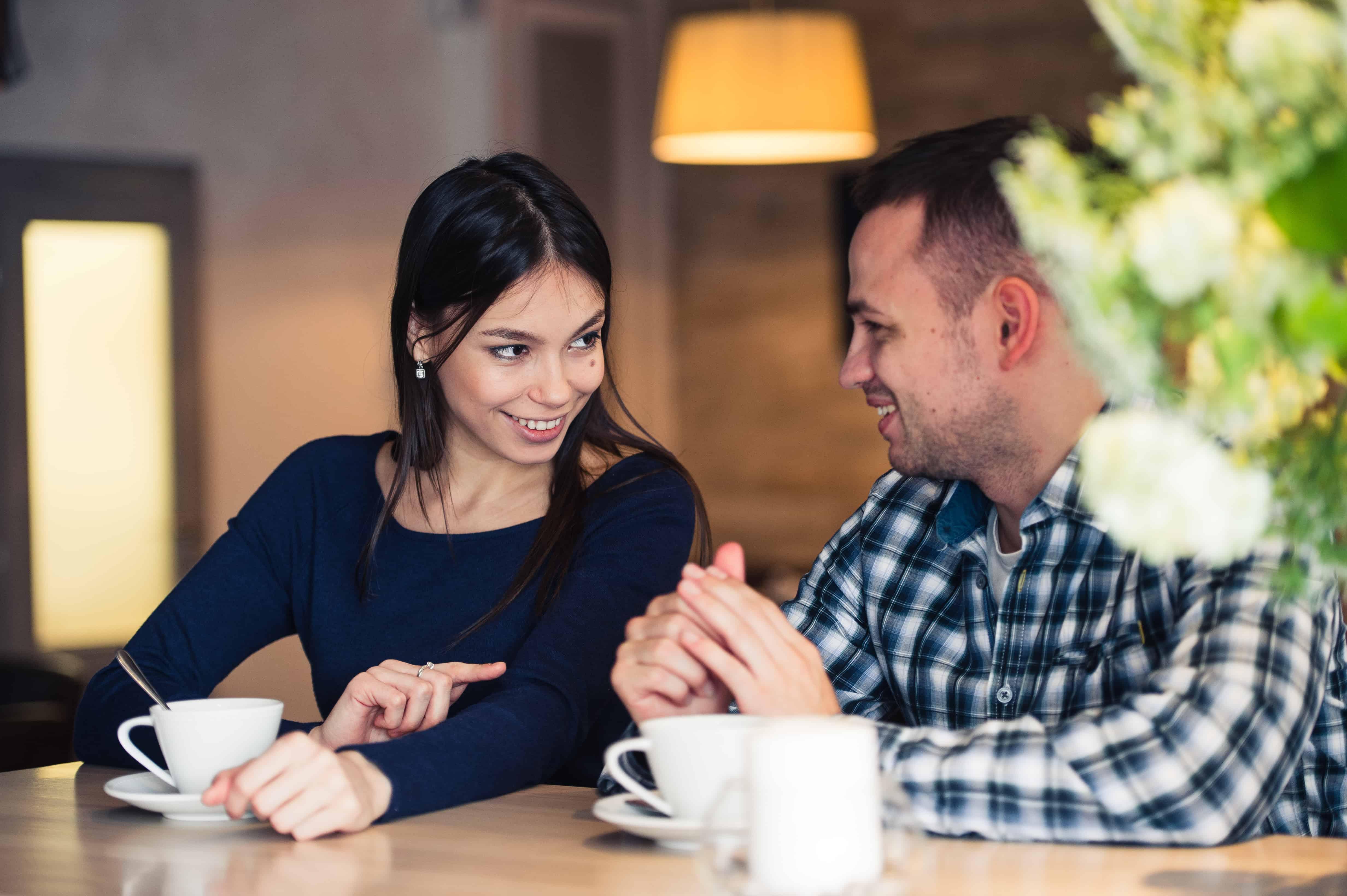 Eine lächelnde Frau, die mit einem Mann im Café über ein Date spricht