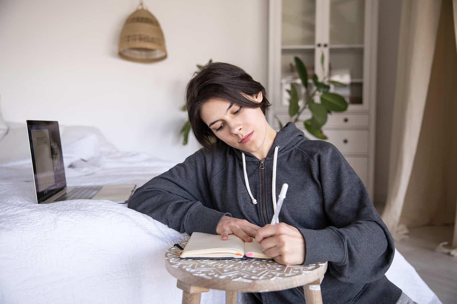 eine nachdenkliche Frau, die in ein Notizbuch schreibt, während sie in der Nähe des Bettes sitzt