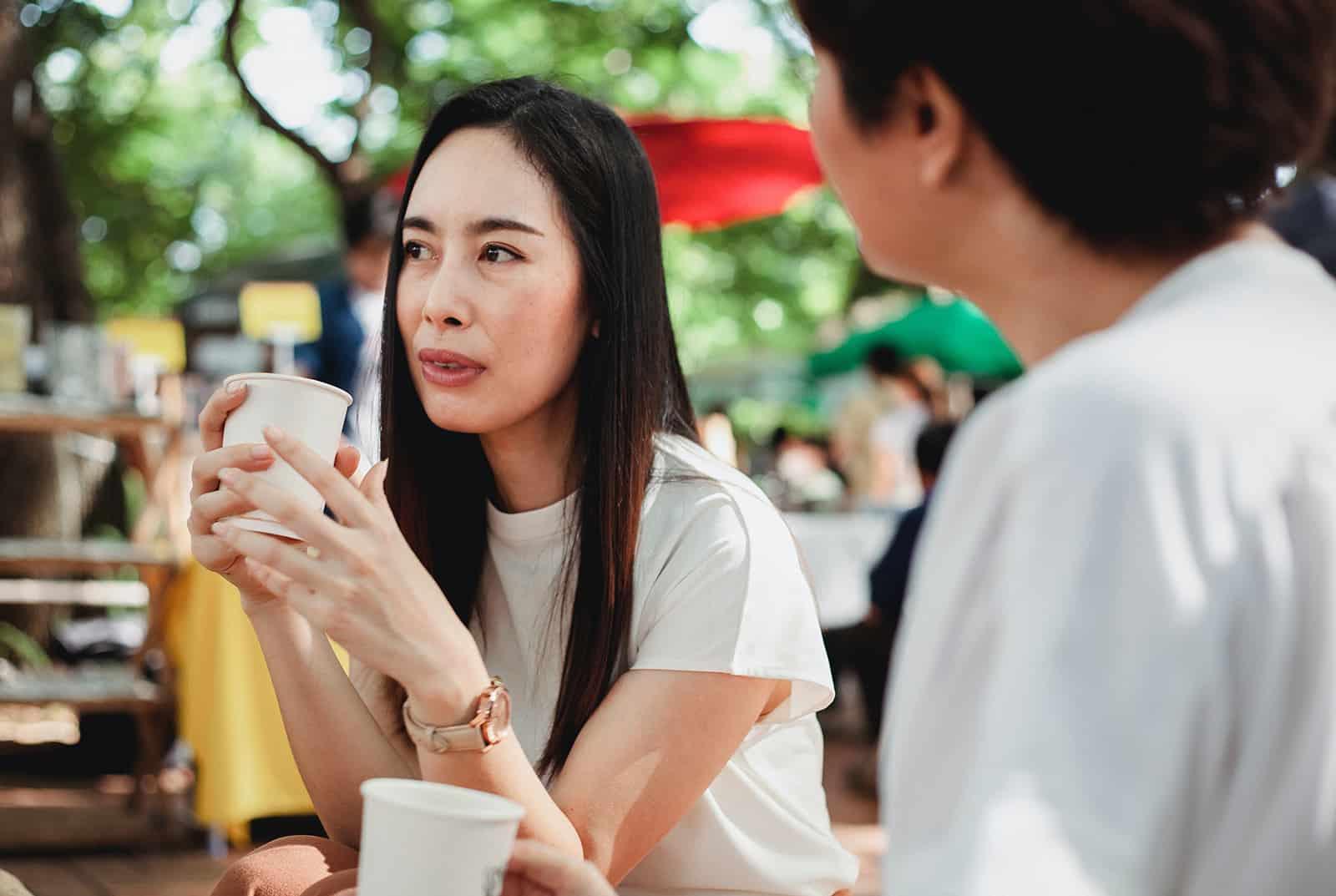 eine nachdenkliche Frau, die mit einer Freundin spricht, während sie zusammen Kaffee trinkt