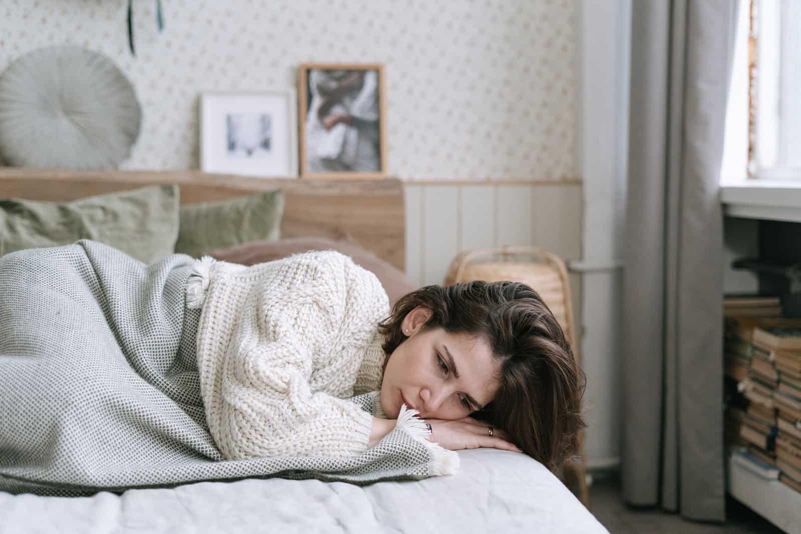 eine traurige Frau, die nach der Trennung auf dem Bett liegt