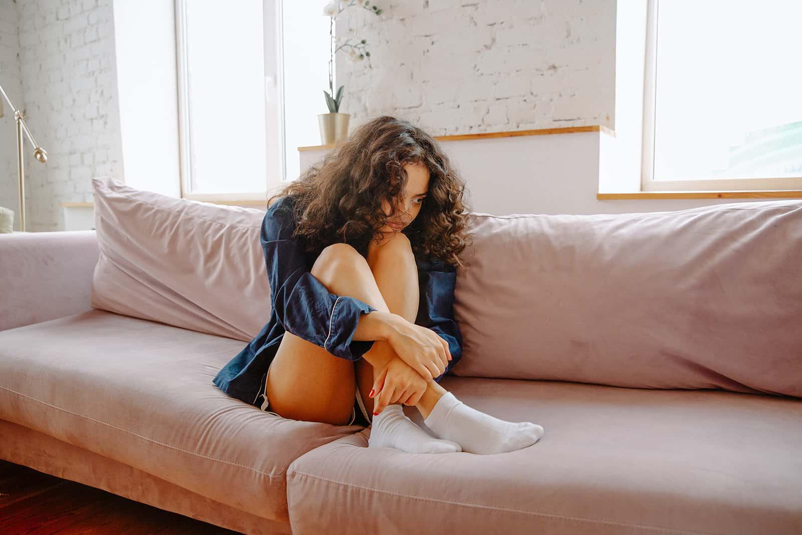 eine traurige Frau sitzt auf der Couch umarmte ihre Knie