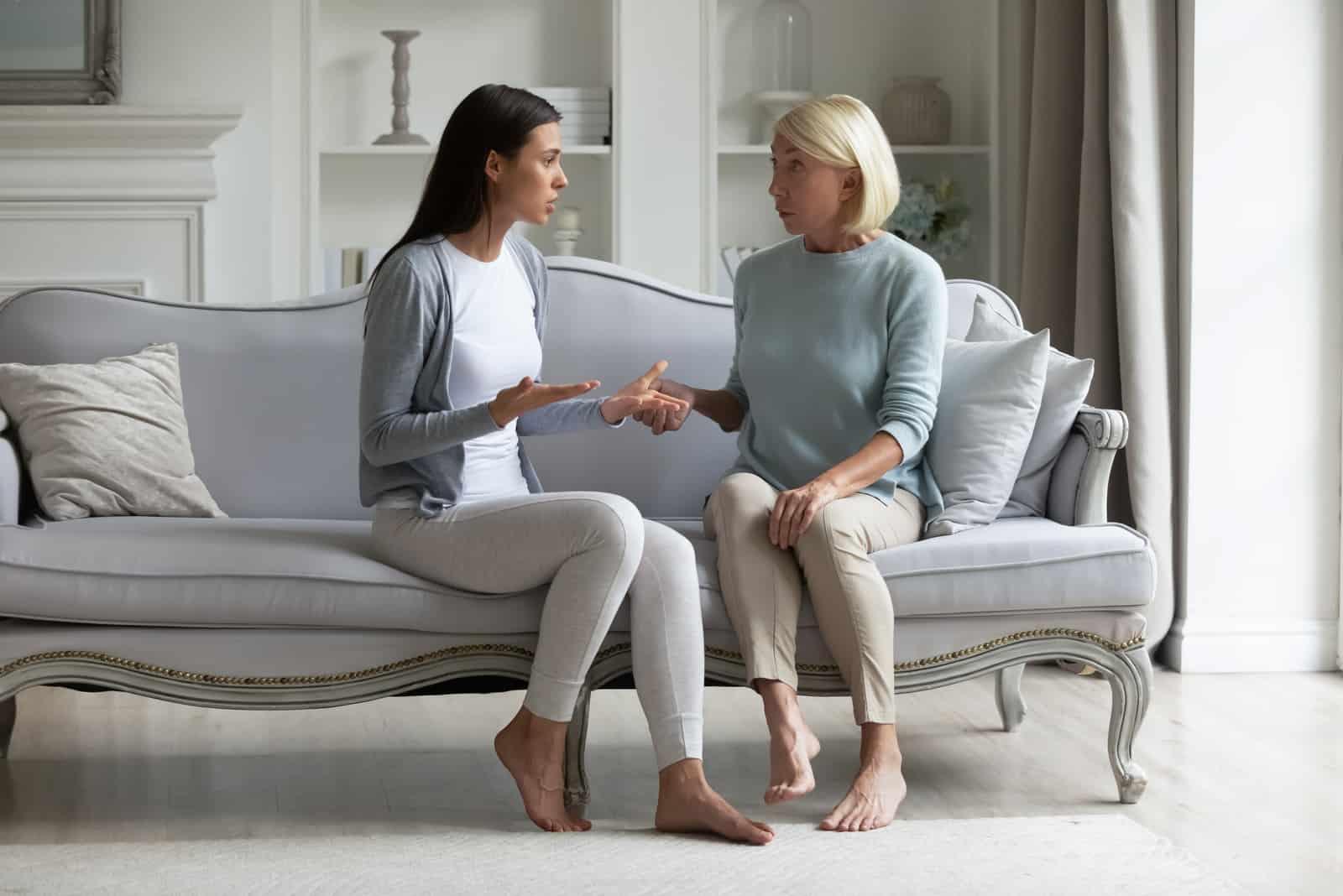 erwachsene Tochter sitzt auf der Couch mit älterer Mutter