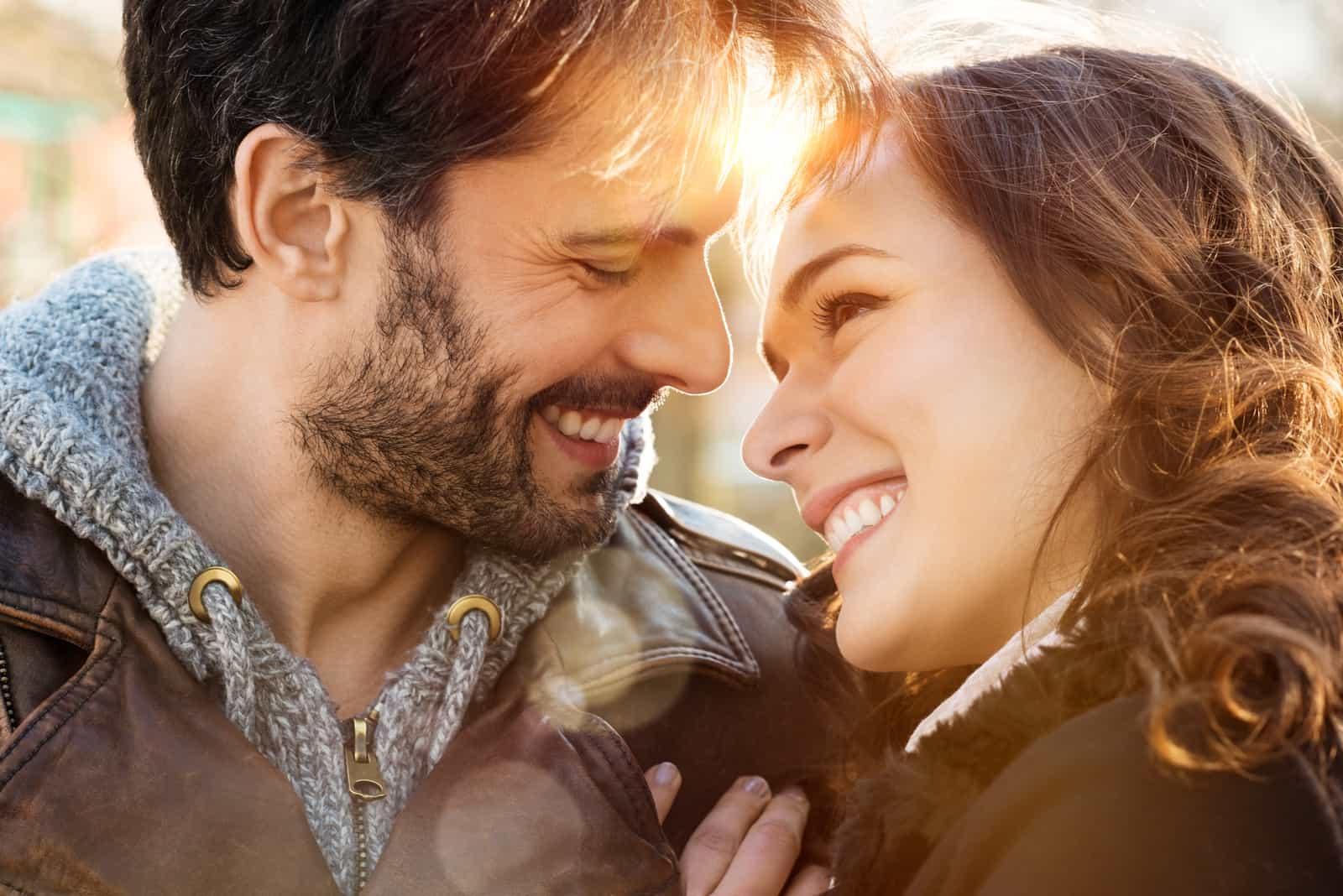 glückliches junges Paar, das einander ansieht und im Freien lächelt