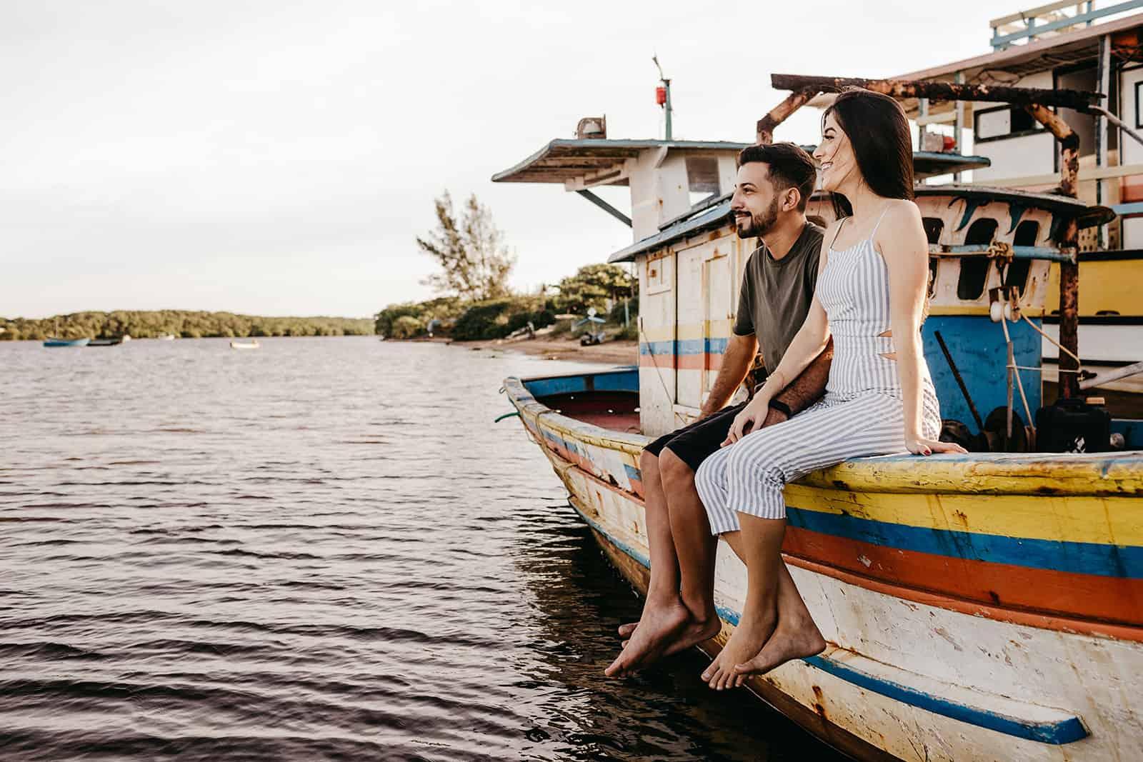 glückliches Paar, das auf dem Boot sitzt und Hände hält