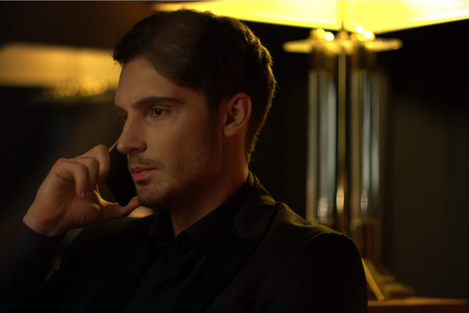 gutaussehender Mann, der an seinem Telefon spricht
