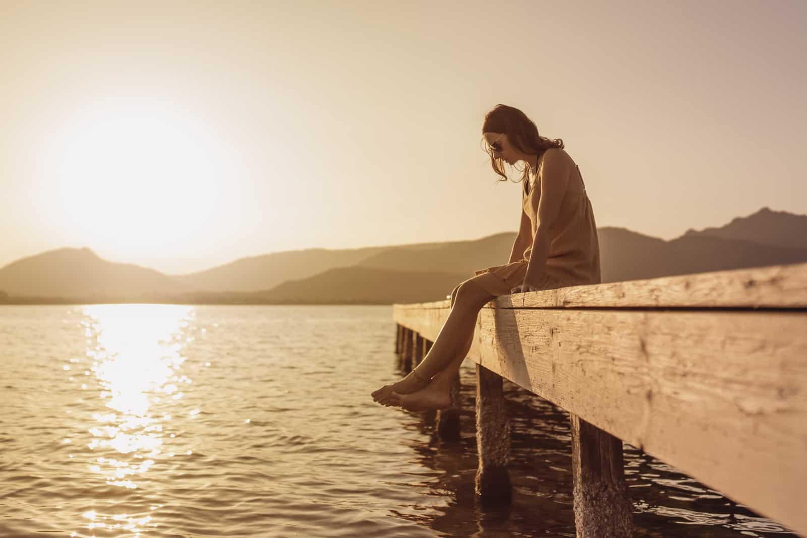 hübsche junge Frau, die auf einem Pier eines Sees sitzt