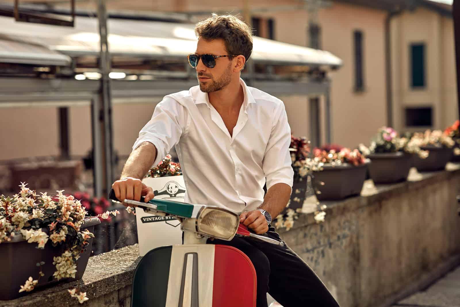 italienischer Mann, der weißes Hemd trägt und auf klassischem Roller sitzt