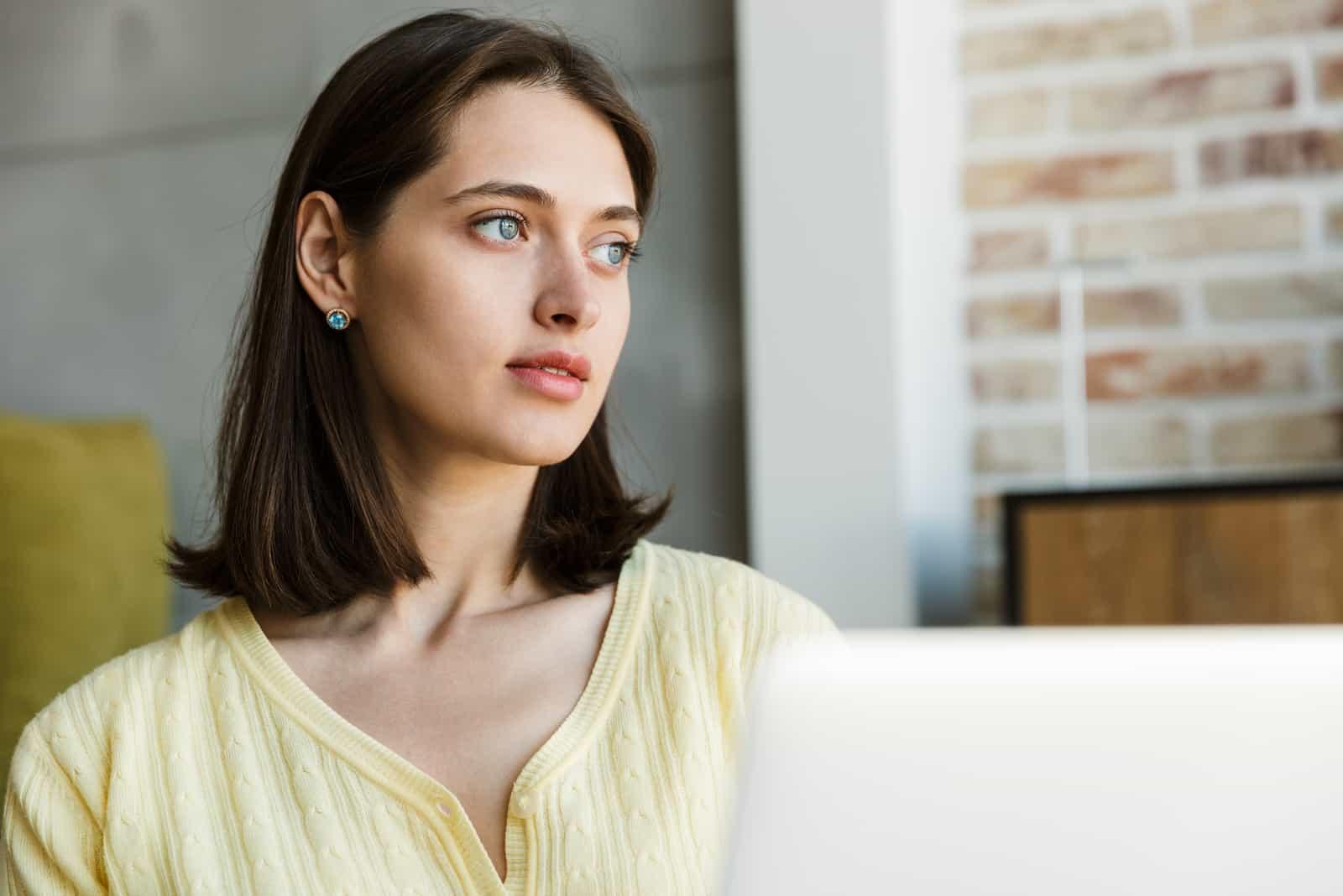 junge brünette Frau, die Laptop-Computer beim Sitzen verwendet