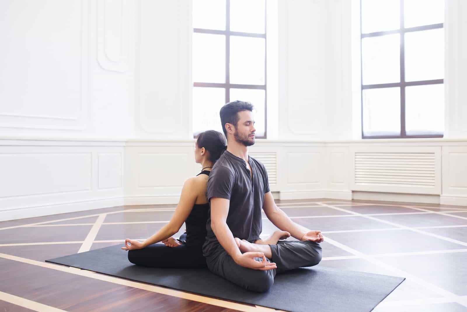 junges Paar, das zusammen Yoga macht