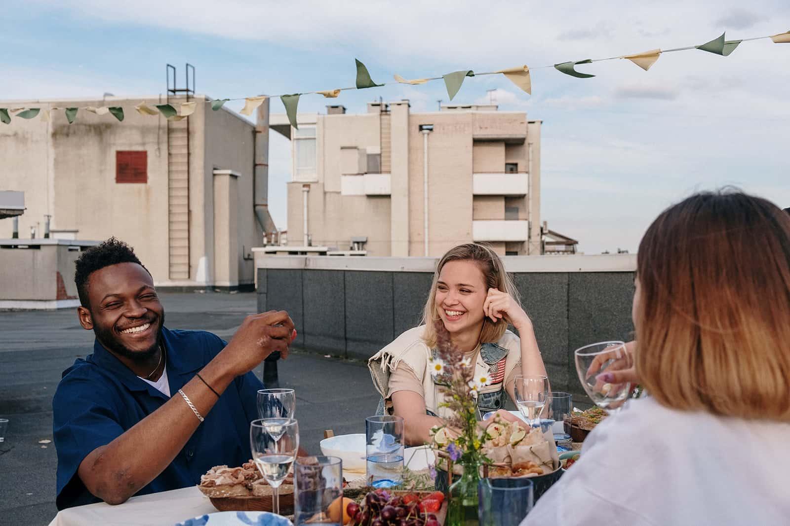 lächelnde Frau, die lächelnden Mann betrachtet mit Freunden am Tisch auf dem Dach sitzen