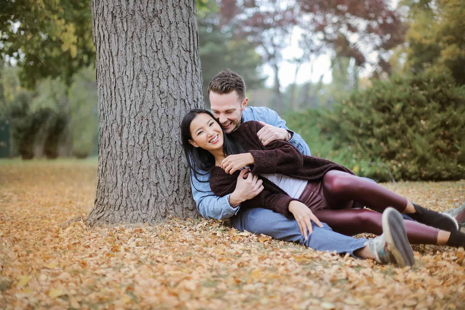 lächelndes Paar sitzt auf den getrockneten Blättern und kuschelt