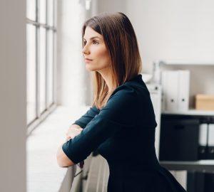 nachdenkliche Frau am Fenster stehen