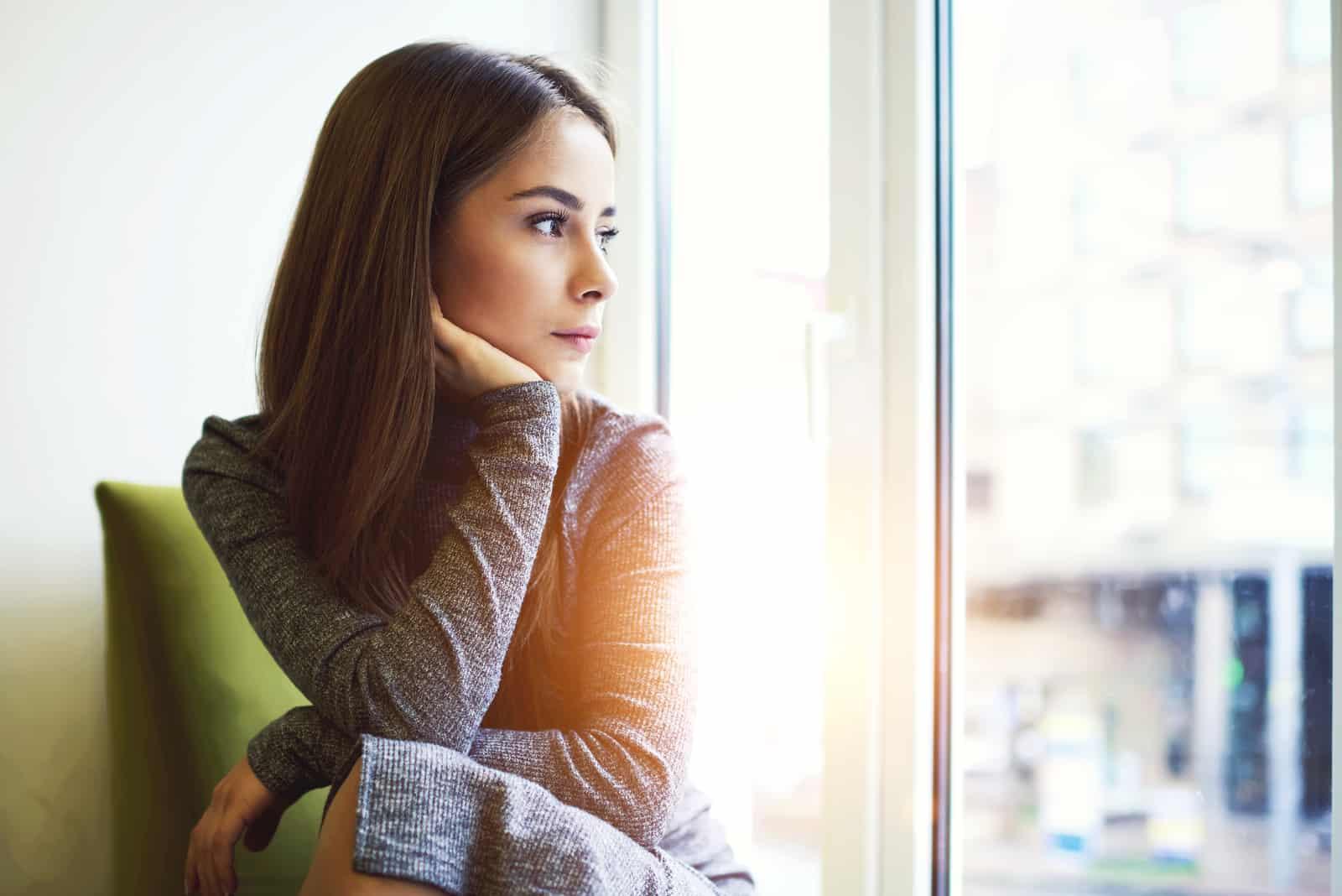 nachdenkliche Frau, die durch das Fenster schaut