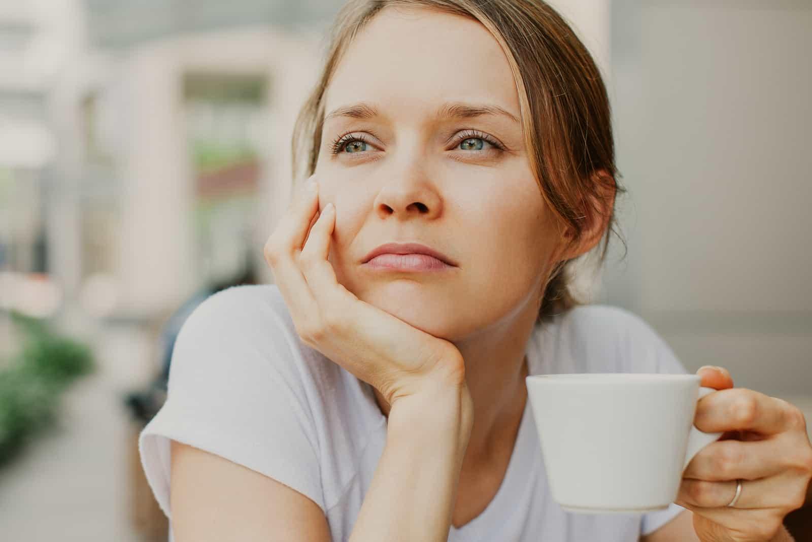 nachdenkliche junge schöne Frau, die Kaffee trinkt